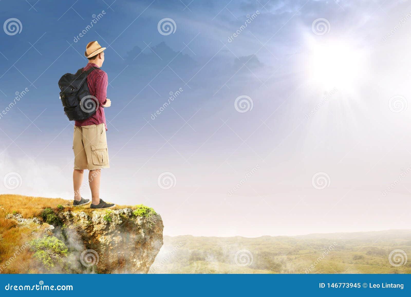 Achtermening van de Aziatische reizigersmens met hoed en rugzak die zich op de rand van klip bevinden die landschappen bekijken