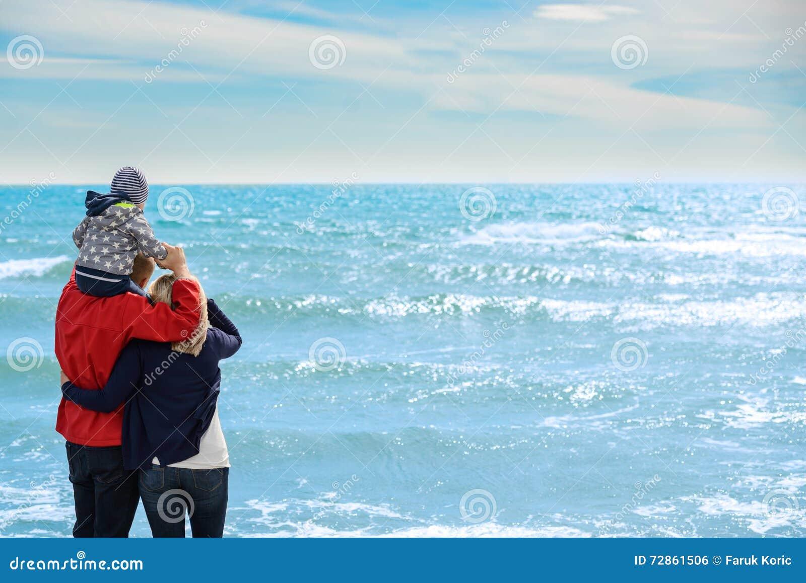 Achtermening van een gelukkige familie bij tropisch strand op de zomervakantie
