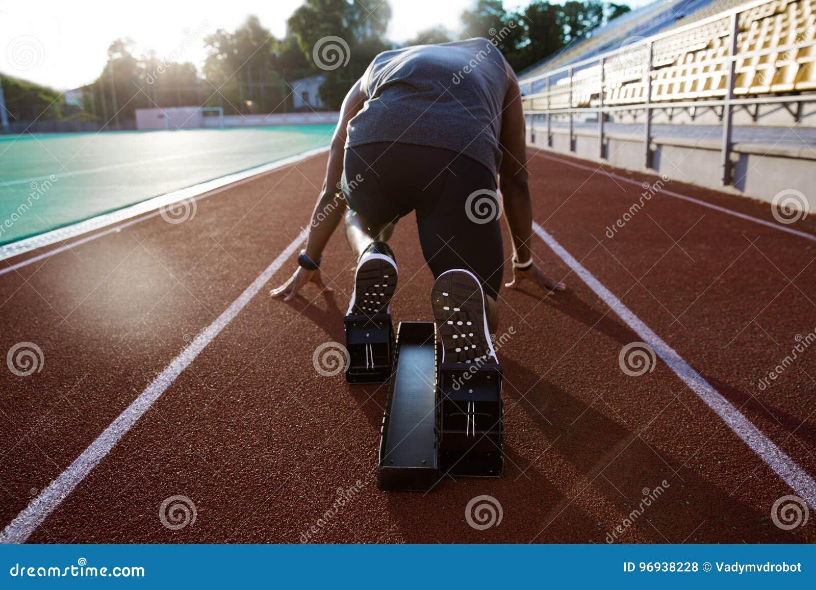 Achtermening van een jonge mannelijke atleet bij startblok