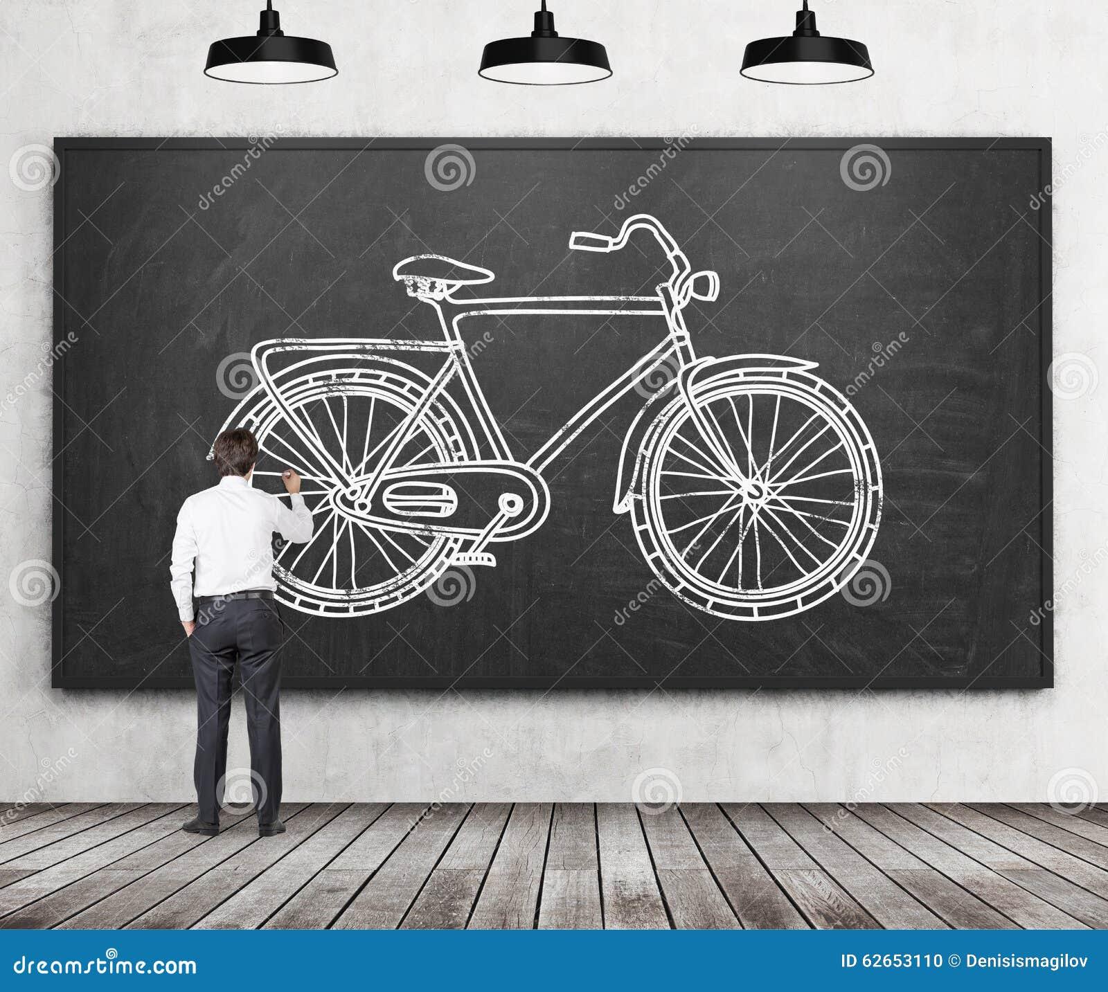 Achtermening van een zakenman in formele kleding die een schets van een fiets op het reusachtige zwarte bord trekt Een concept en