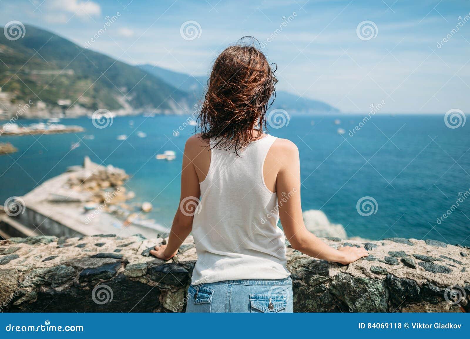 Achtermening van jonge vrouw die van mooi zeegezicht in Italië genieten