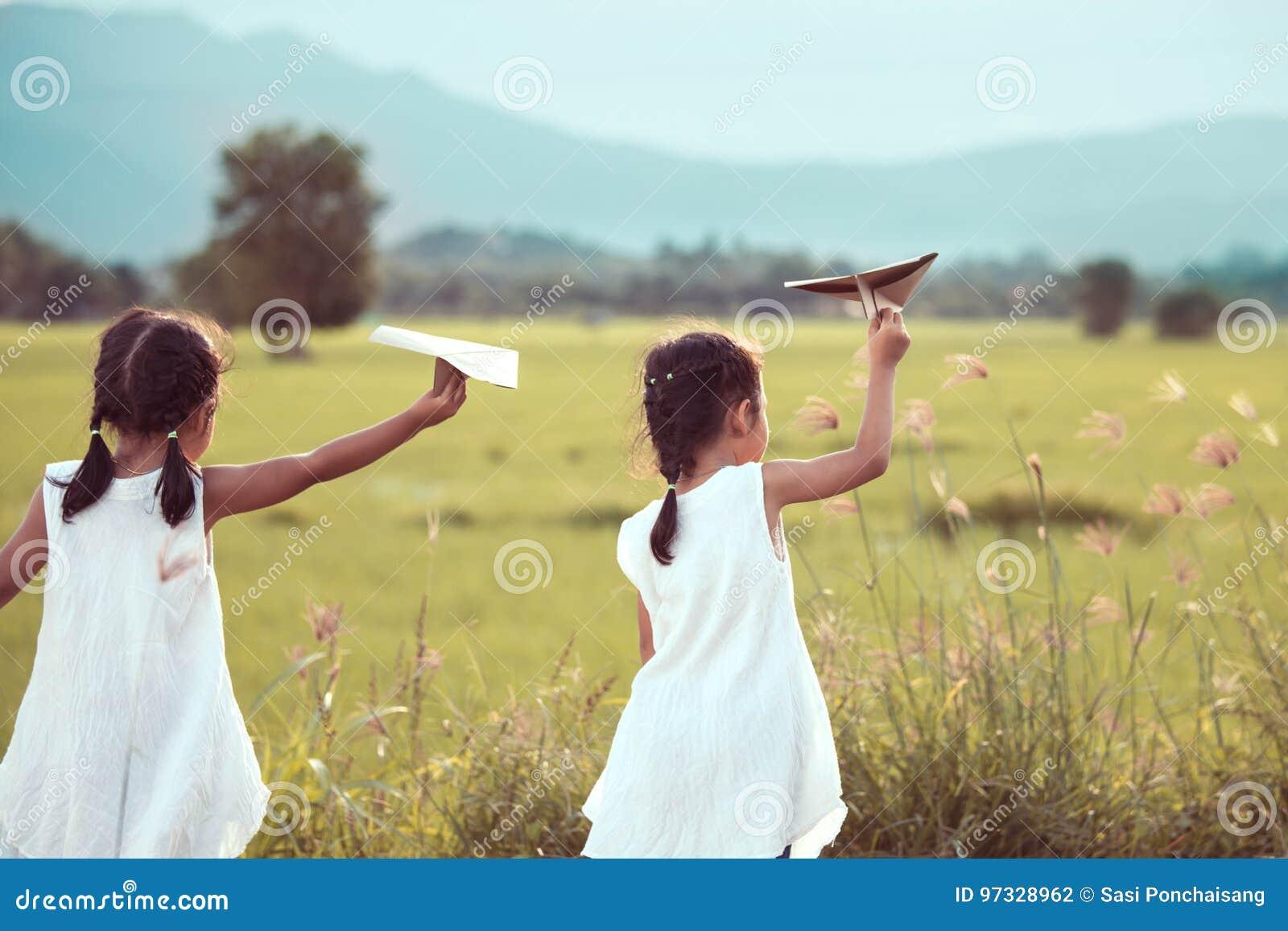 Achtermening van twee Aziatische kindmeisjes die stuk speelgoed document vliegtuig spelen