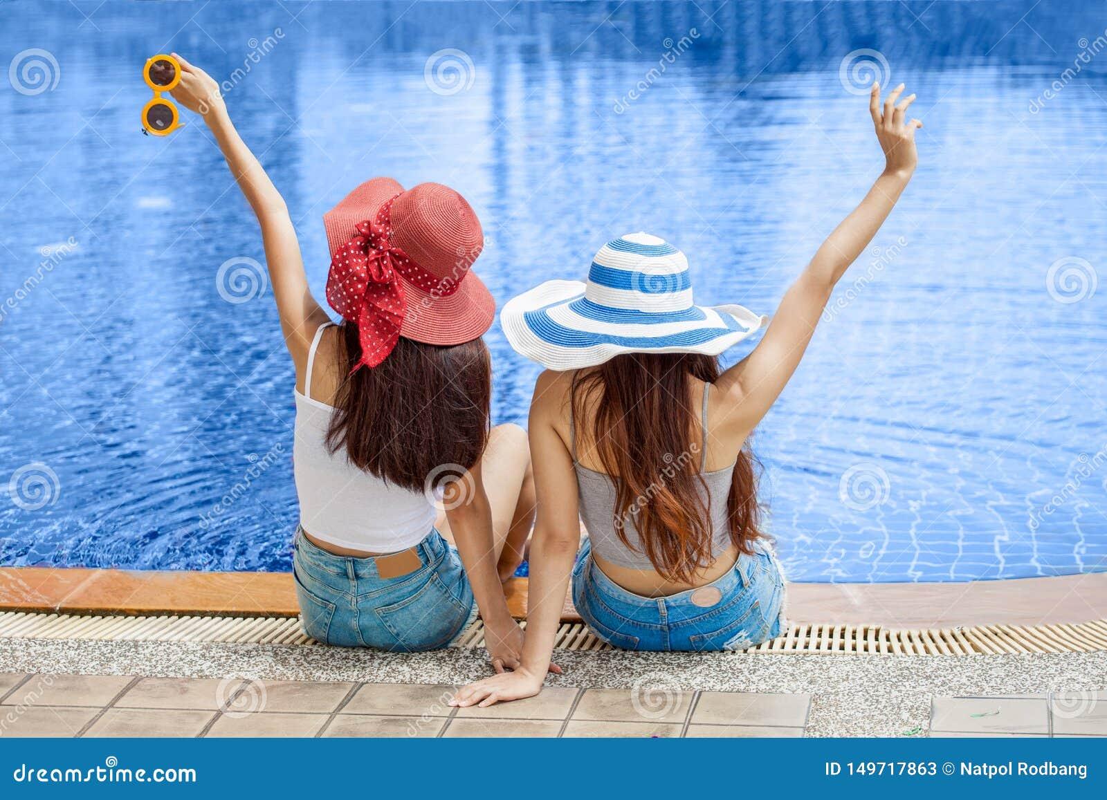 Achtermening van twee mooie Jonge Aziatische vrouwen in grote de zomerhoed en zonnebril die op de rand van het zwembad met voeten