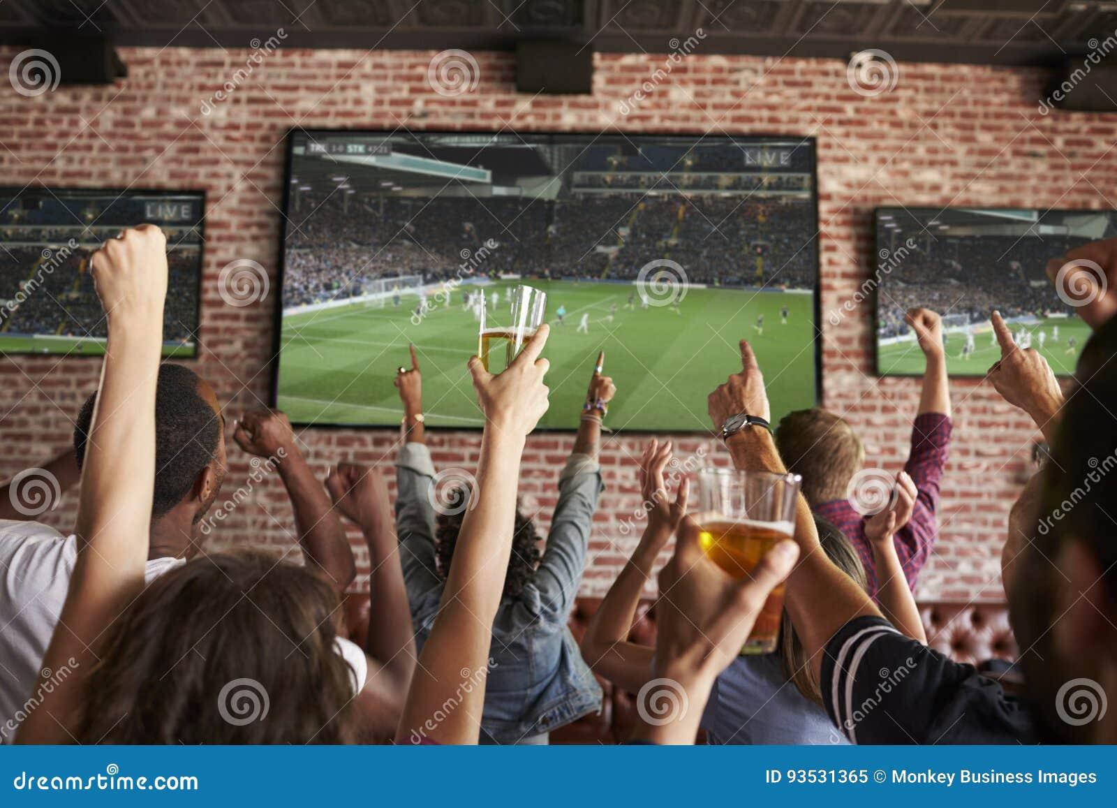Achtermening van Vrienden die op Spel in Sportenbar letten op de Schermen