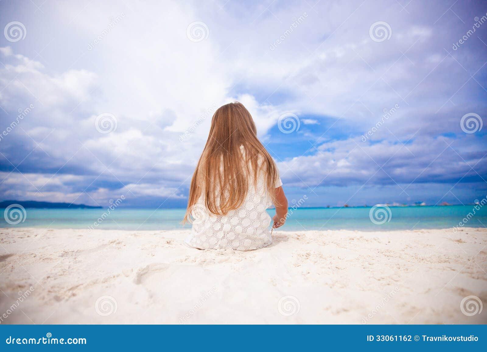 Achtermening van weinig leuk meisje die op het strand siiting