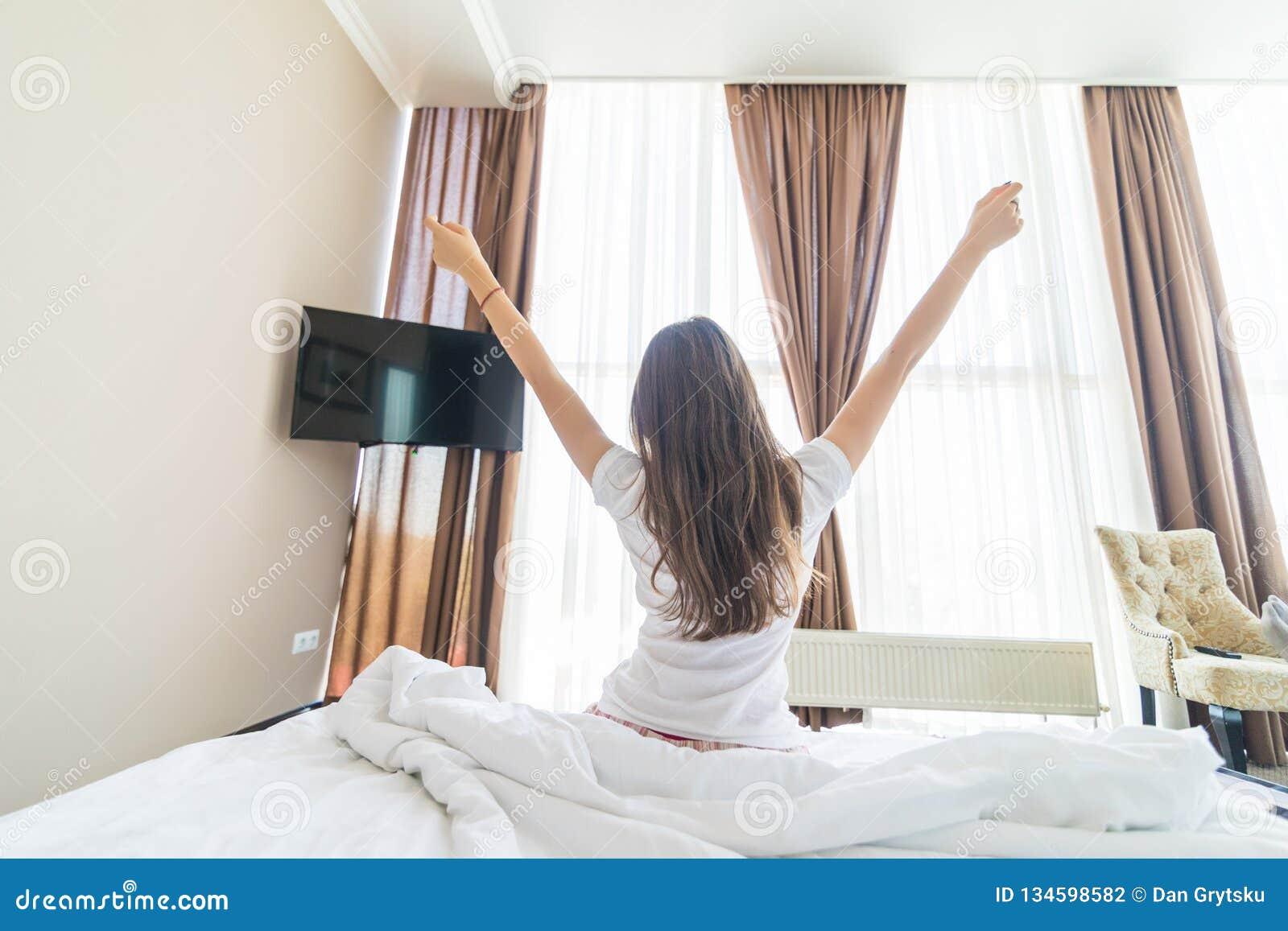 Achtermening van zich het jonge vrouw uitrekken in bed na kielzog omhoog in ochtend met zonlicht