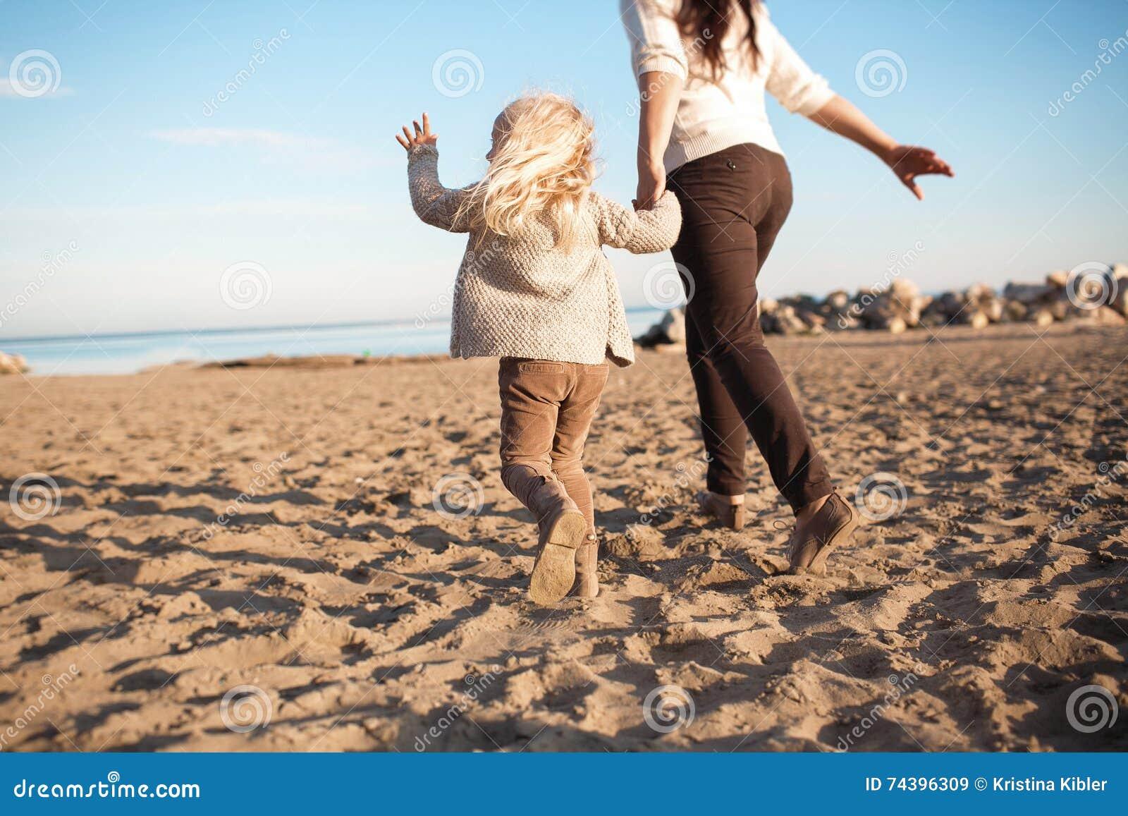 ACHTERmening: Weinig dochter loopt met zijn moeder op een strand