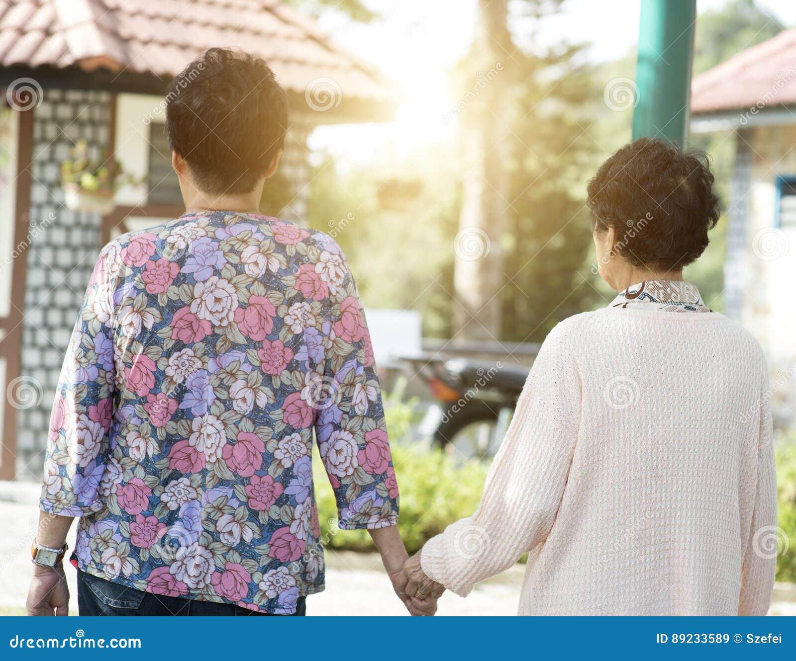 Achtermenings Aziatische bejaarden die bij openluchtpark lopen