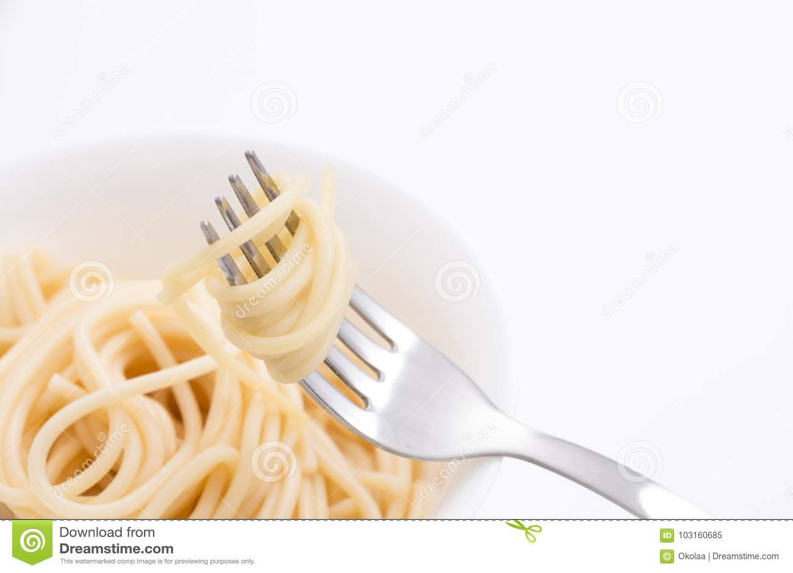 Aclare las pastas cocinadas de los espaguetis en el cuenco blanco y en la bifurcación, en el fondo blanco