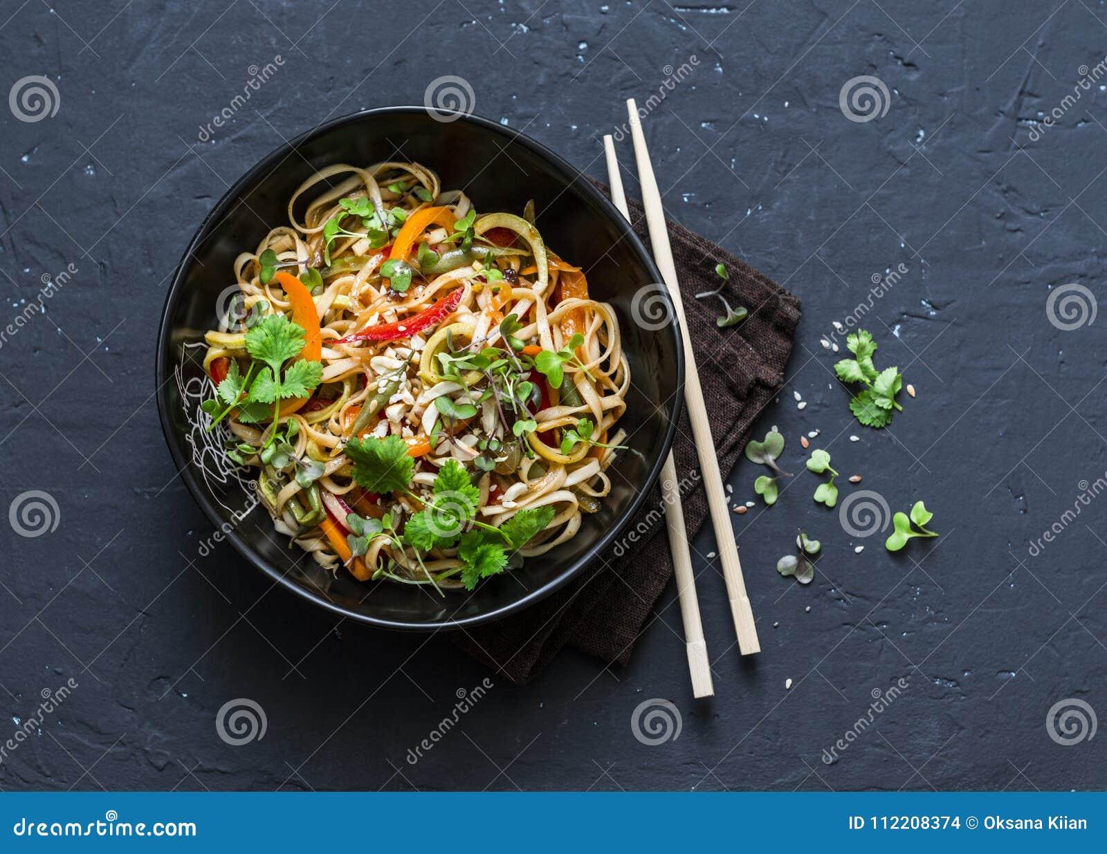 Acolchoe macarronetes tailandeses do udon dos vegetais do vegetariano em um fundo escuro, vista superior Alimento do vegetariano