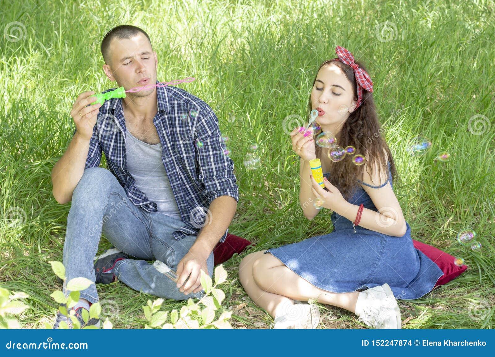 Acople amantes fundem bolhas os amigos riem o menino e a menina do piquenique do verão estão sentando-se na grama