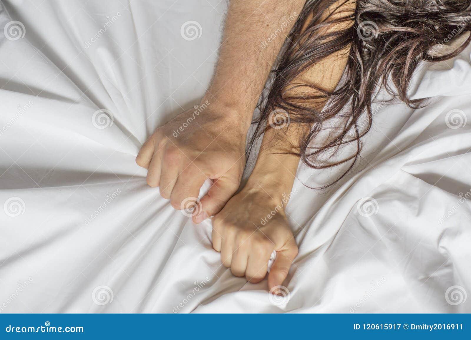 Acople as mãos que puxam as folhas brancas na êxtase, orgasmo Conceito da paixão Oorgasm Momentos eróticos conceito íntimo sexo