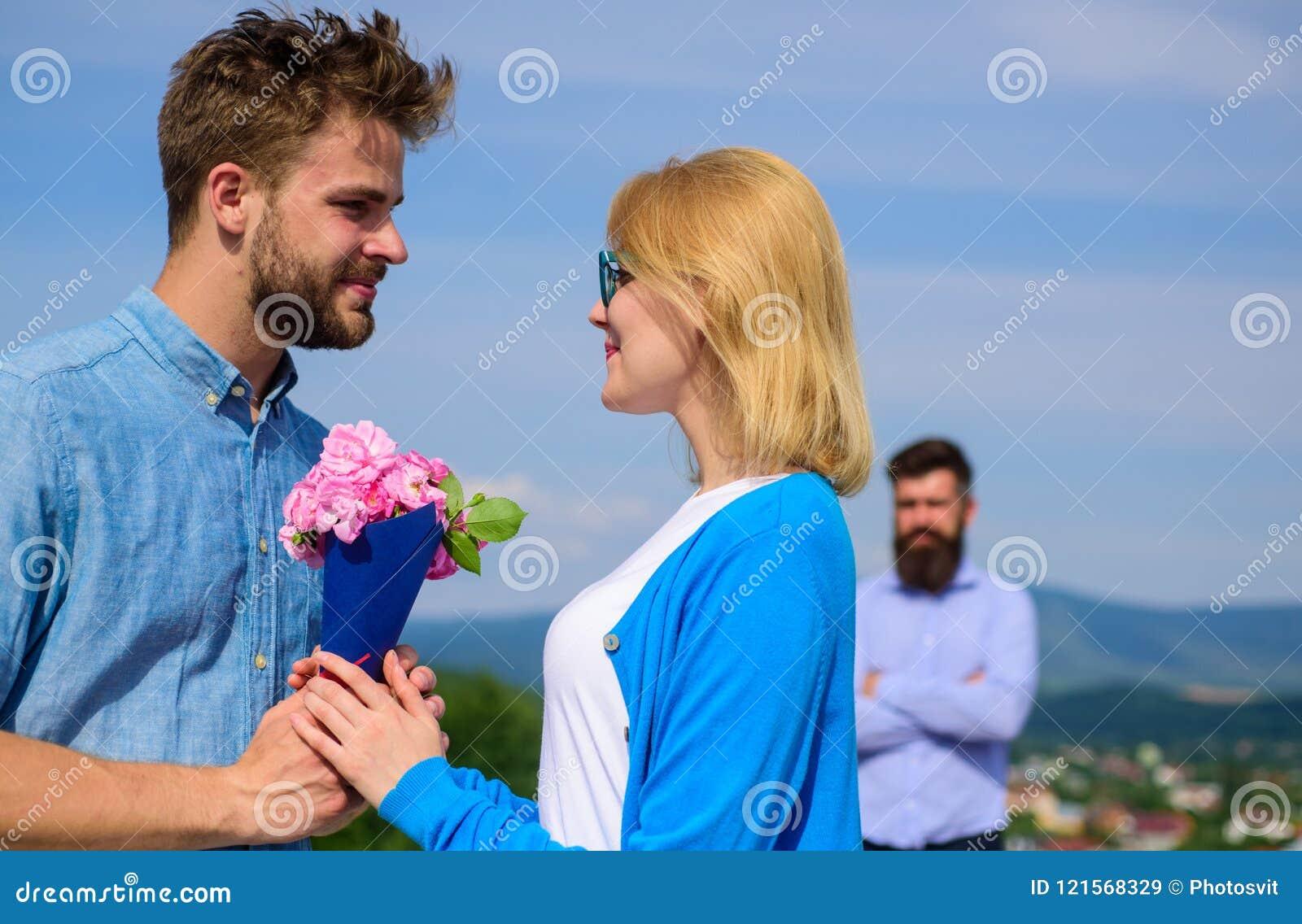 Acople com data romântica do ramalhete das flores Amor novo Pares no amor que data o dia ensolarado exterior, fundo do céu Sócio
