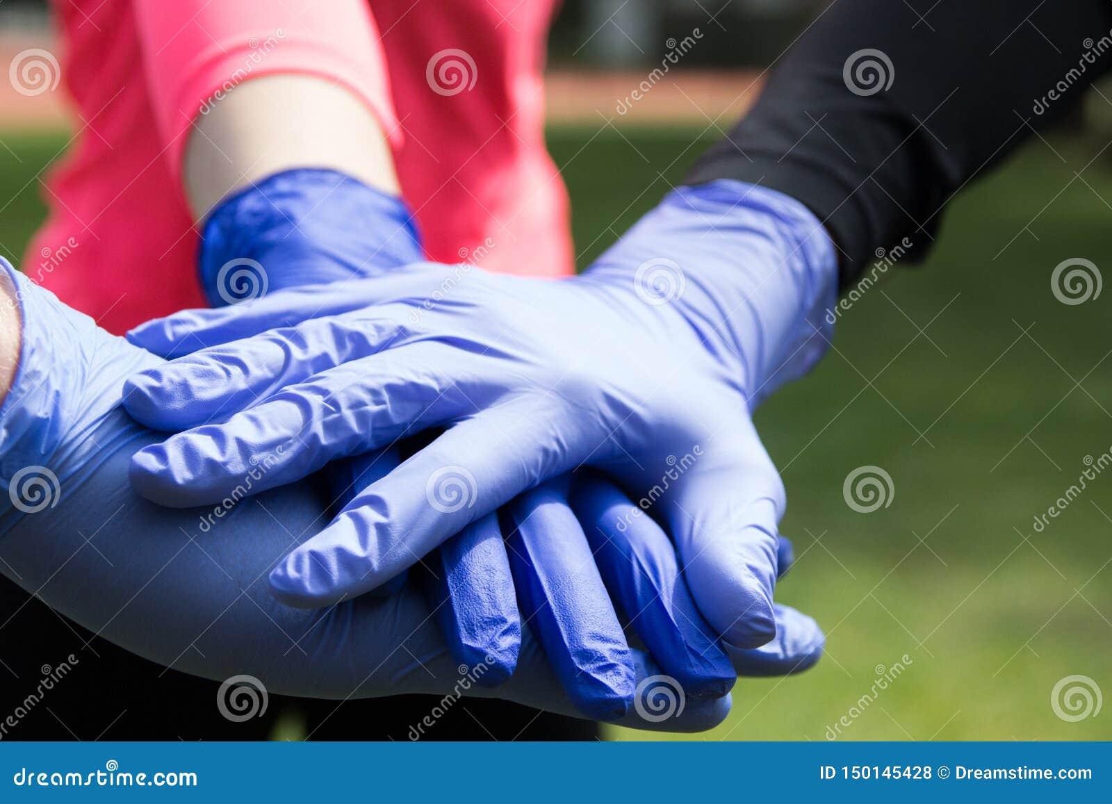 Acople das mãos nas luvas médicas do látex