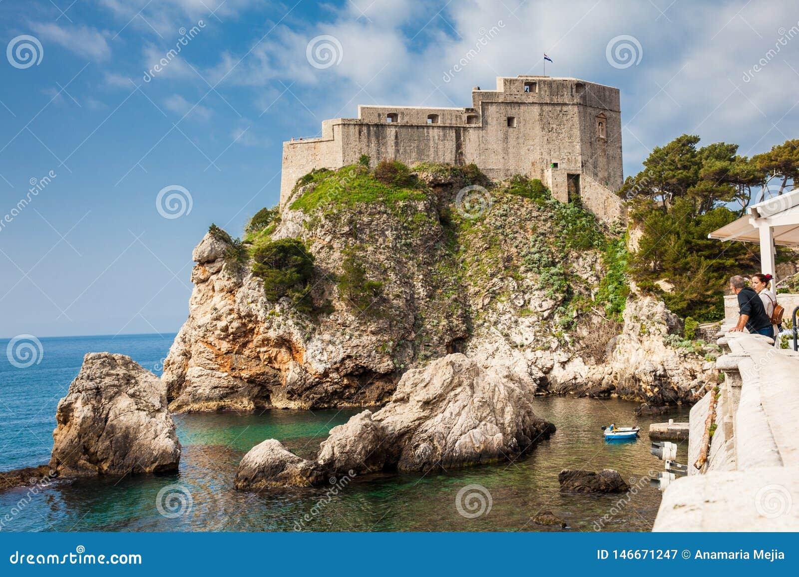 Acople dos turistas que olham o cais ocidental de Dubrovnik e o forte medieval Lovrijenac situado na parede ocidental da cidade