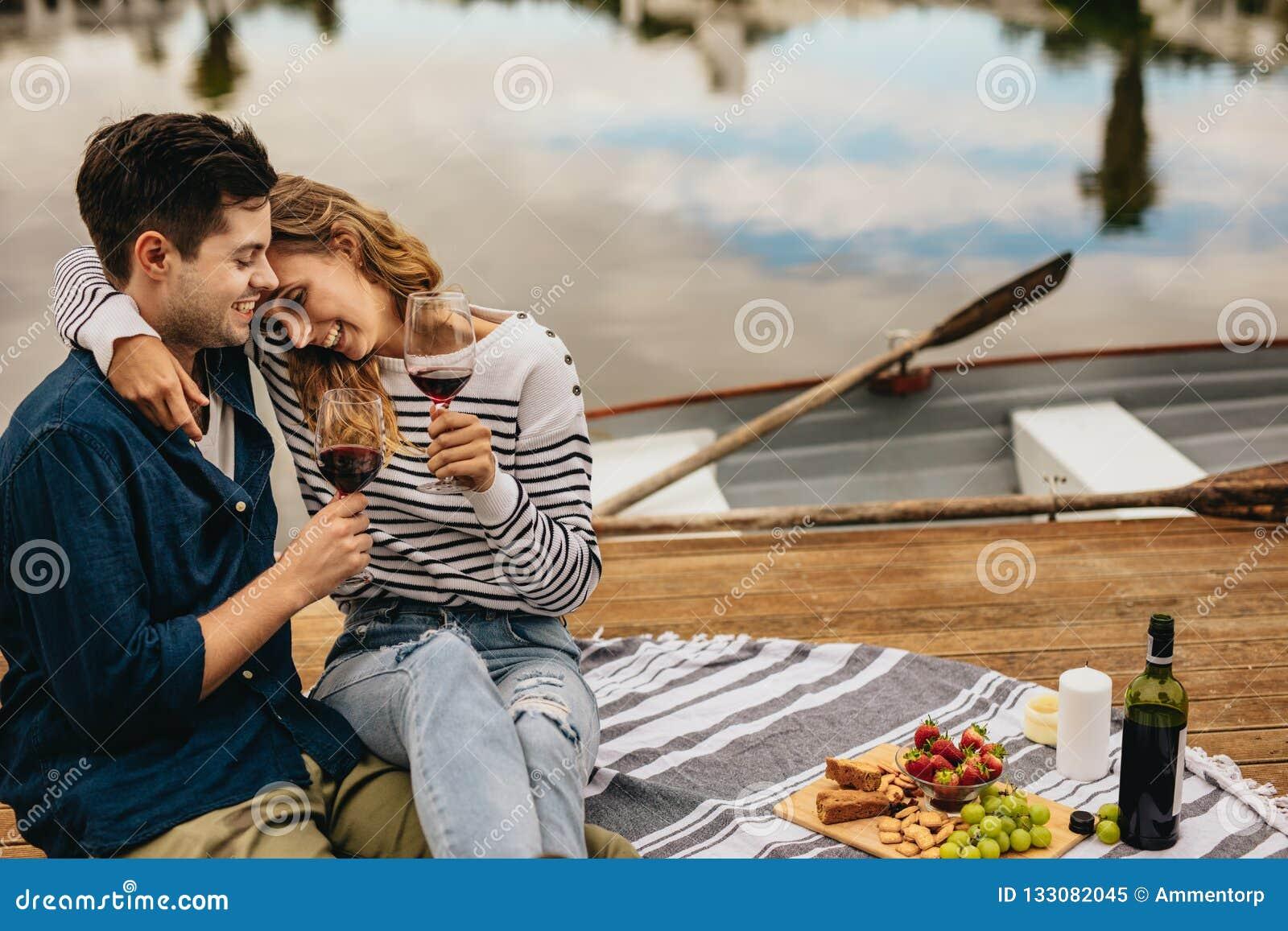 Acople em uma data que senta-se junto ao lado de um vinho bebendo do lago