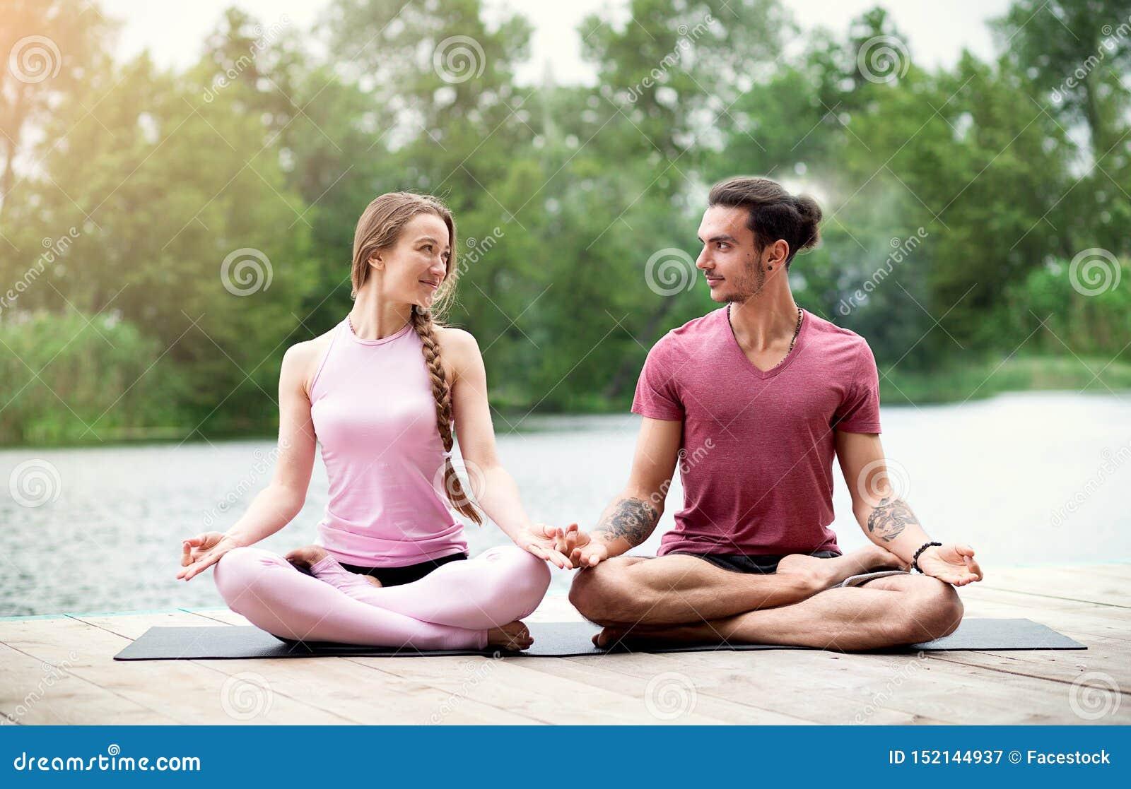 Acople a ioga praticando e a vista de se na natureza perto do rio Medita??o dos pares
