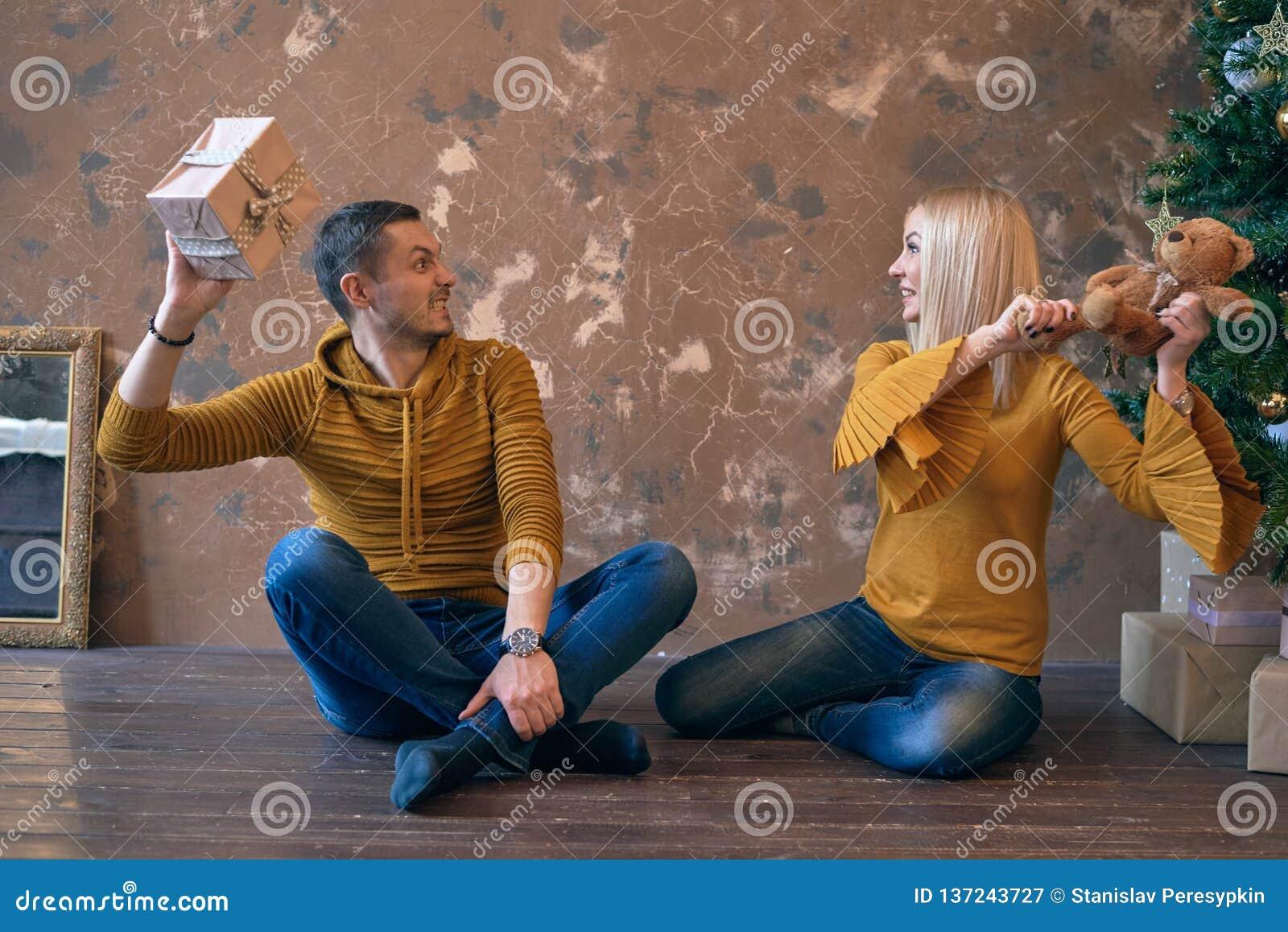 Acople lutas com presentes perto da parede marrom