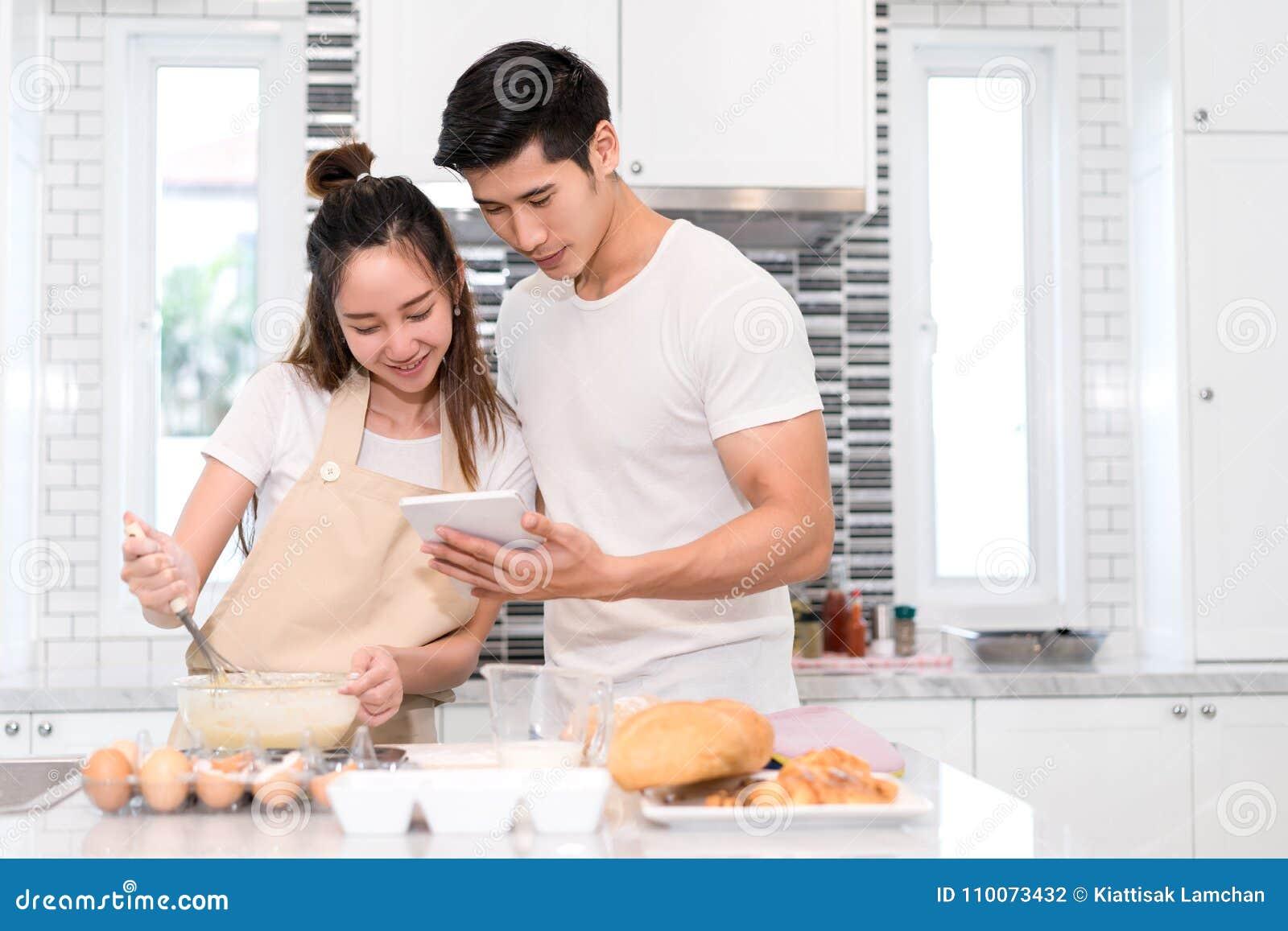 Acople o cozimento da padaria na sala da cozinha, no homem asiático novo e na mulher junto