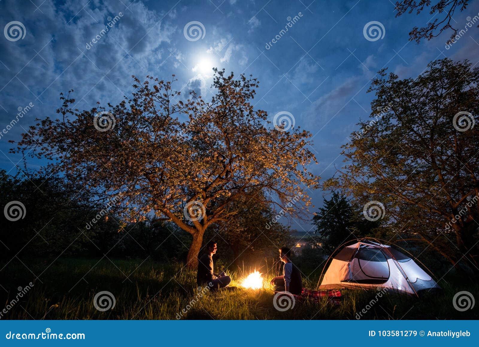 Acople os turistas que sentam-se em uma fogueira perto da barraca sob árvores e do céu noturno com a lua Acampamento da noite