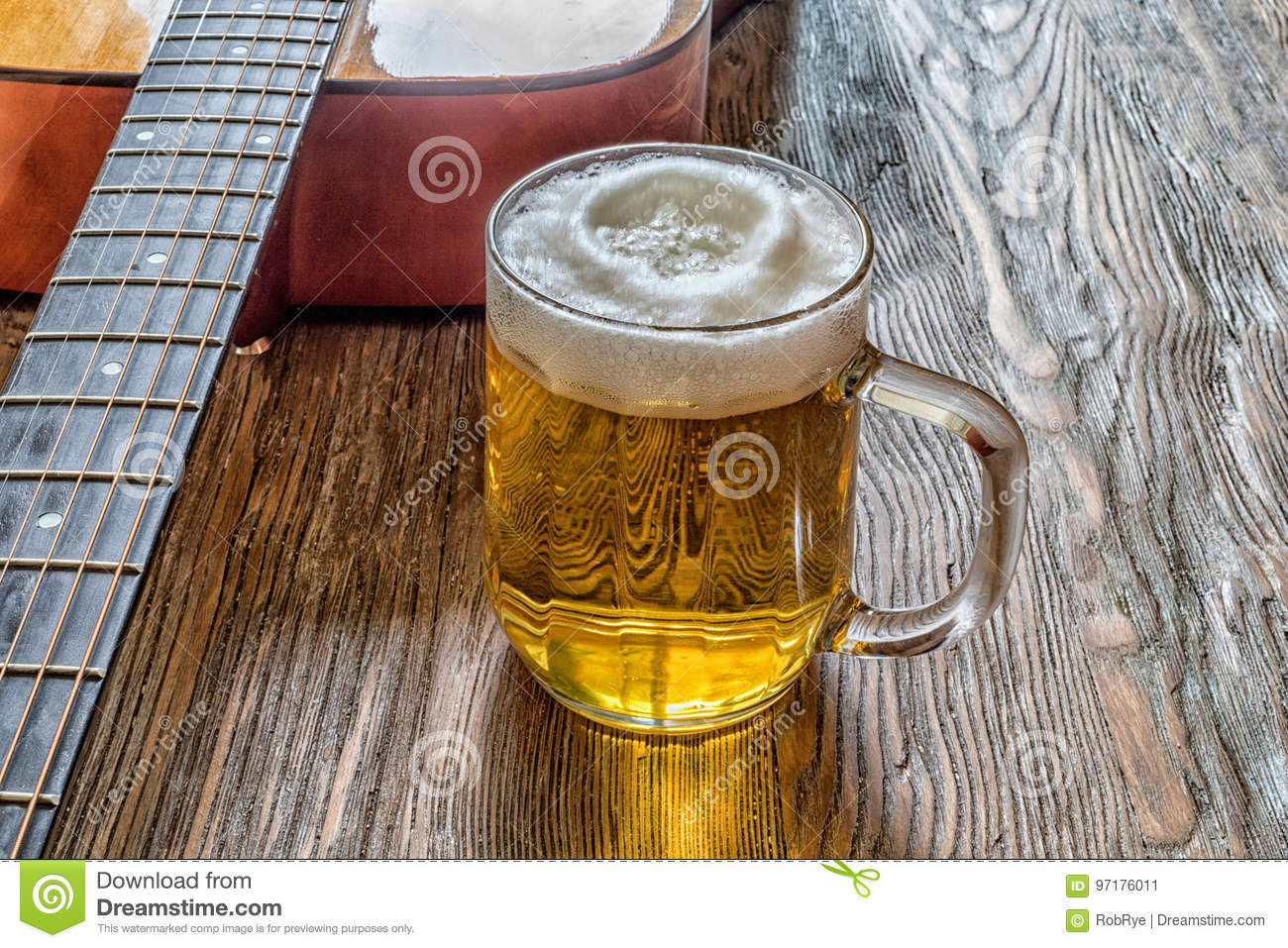 acoustic guitar and beer on an old wooden background stock image