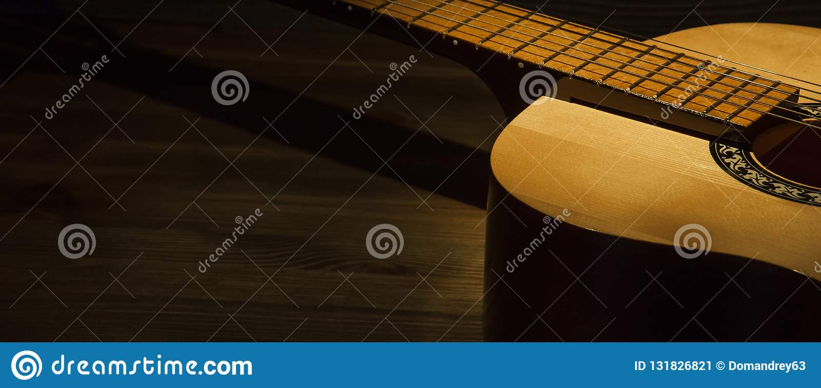 Acoustic guitar on a wooden table lit by a ray of light. Side view