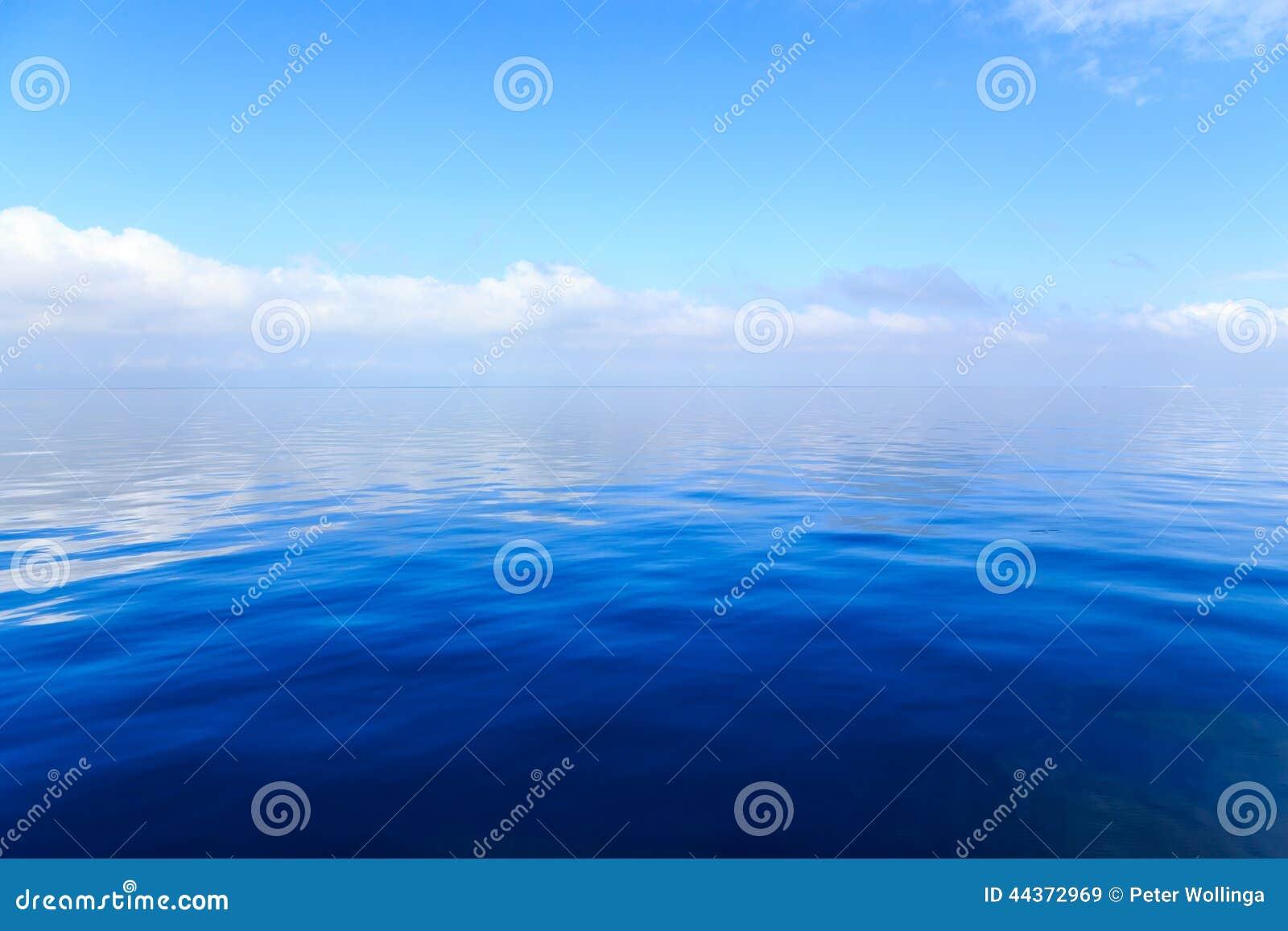 Acqua blu dell oceano con le nuvole nei precedenti