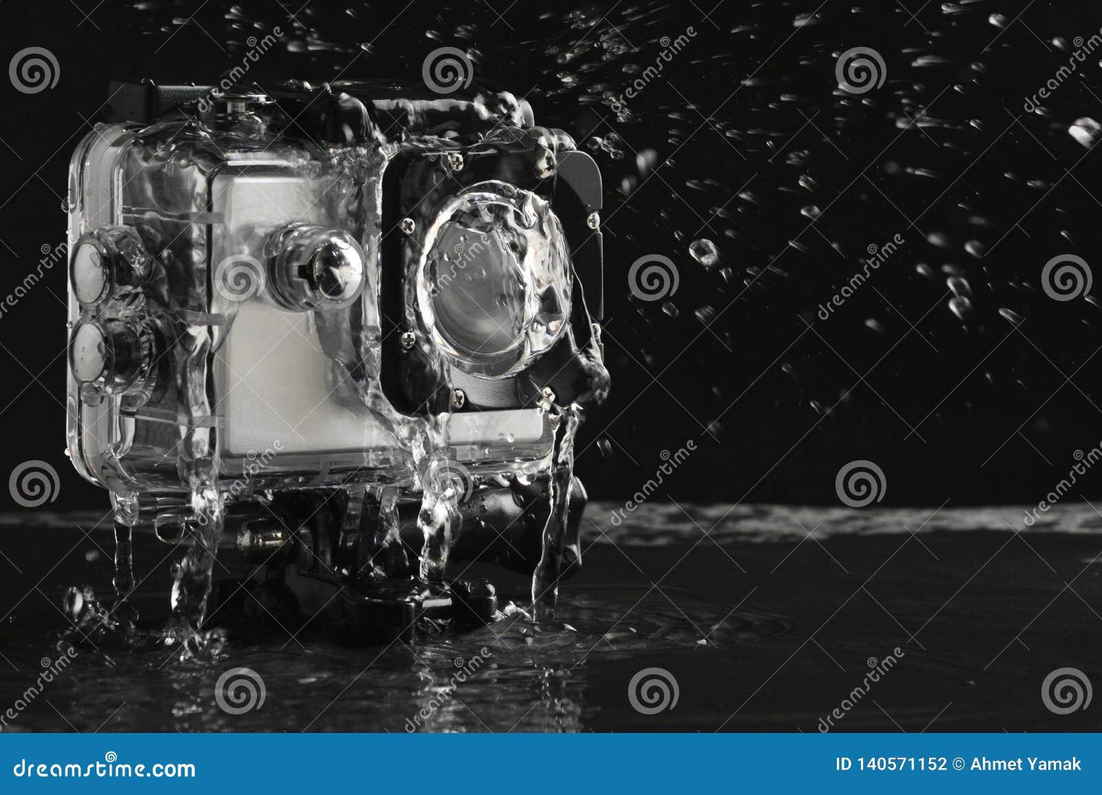 Acqua corrente sulla macchina fotografica impermeabile di azione su fondo di pietra nero bagnato