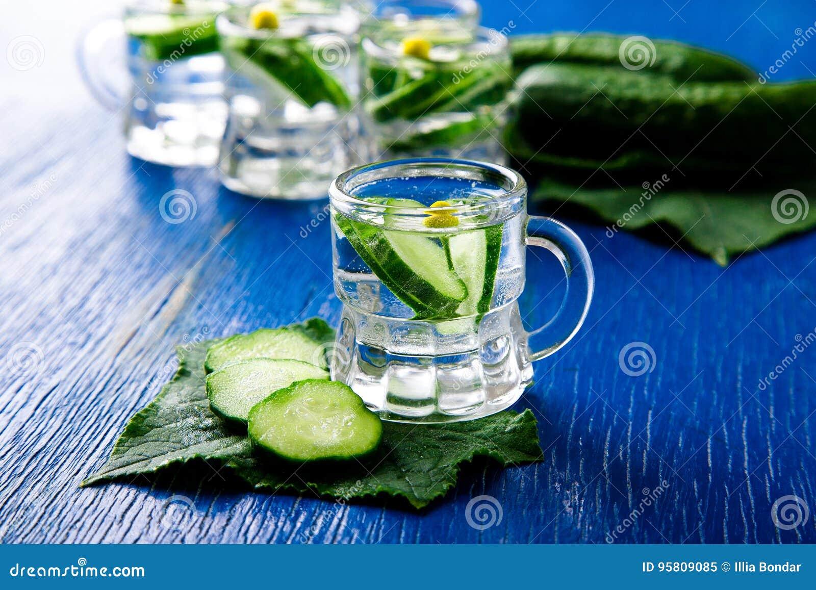 Acqua del cetriolo in barattolo di vetro del piccolo muratore su fondo blu rustic