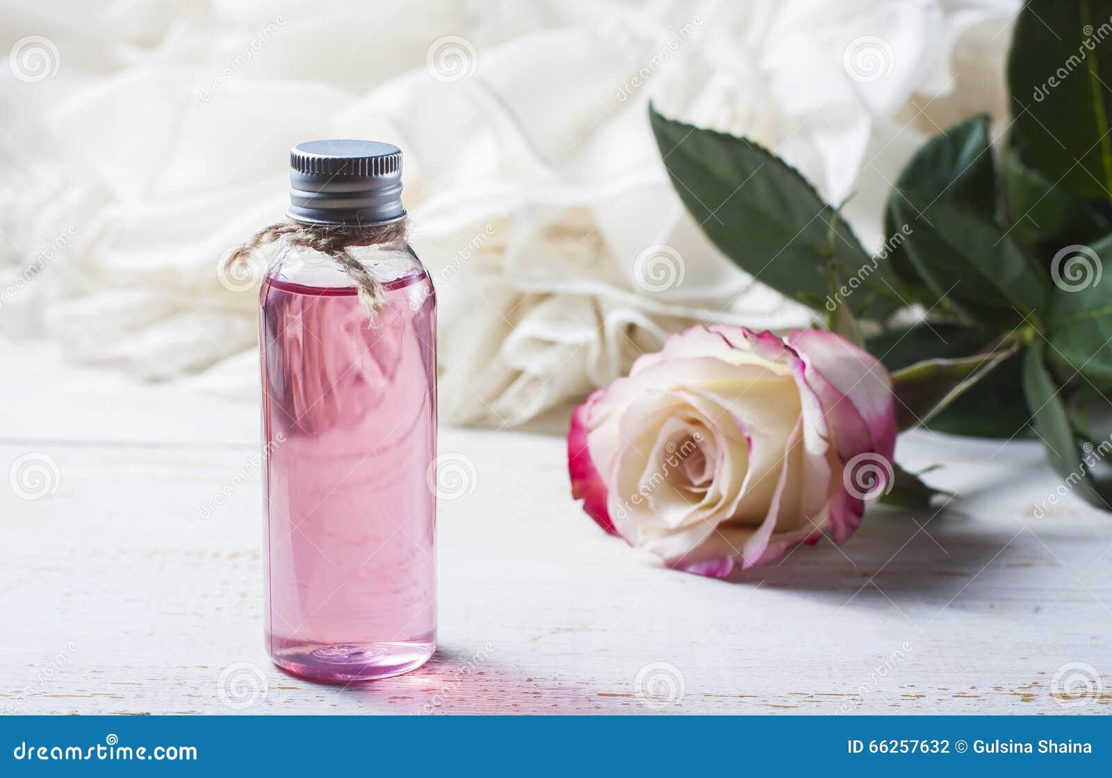 Acqua di rose profumata in una bottiglia su una tavola di legno
