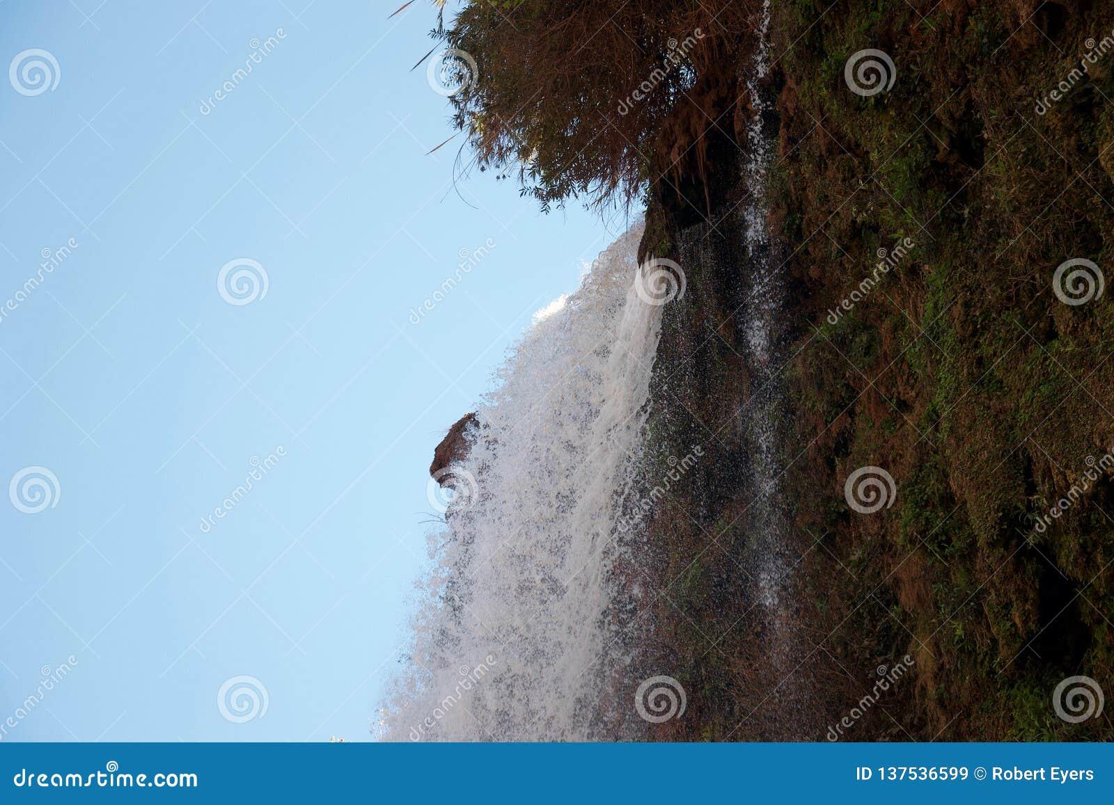 Acqua di schiumatura che immerge sopra un bordo della scogliera