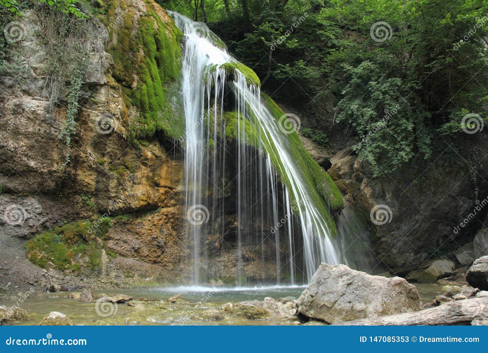Acqua fredda di versamento della cascata della montagna