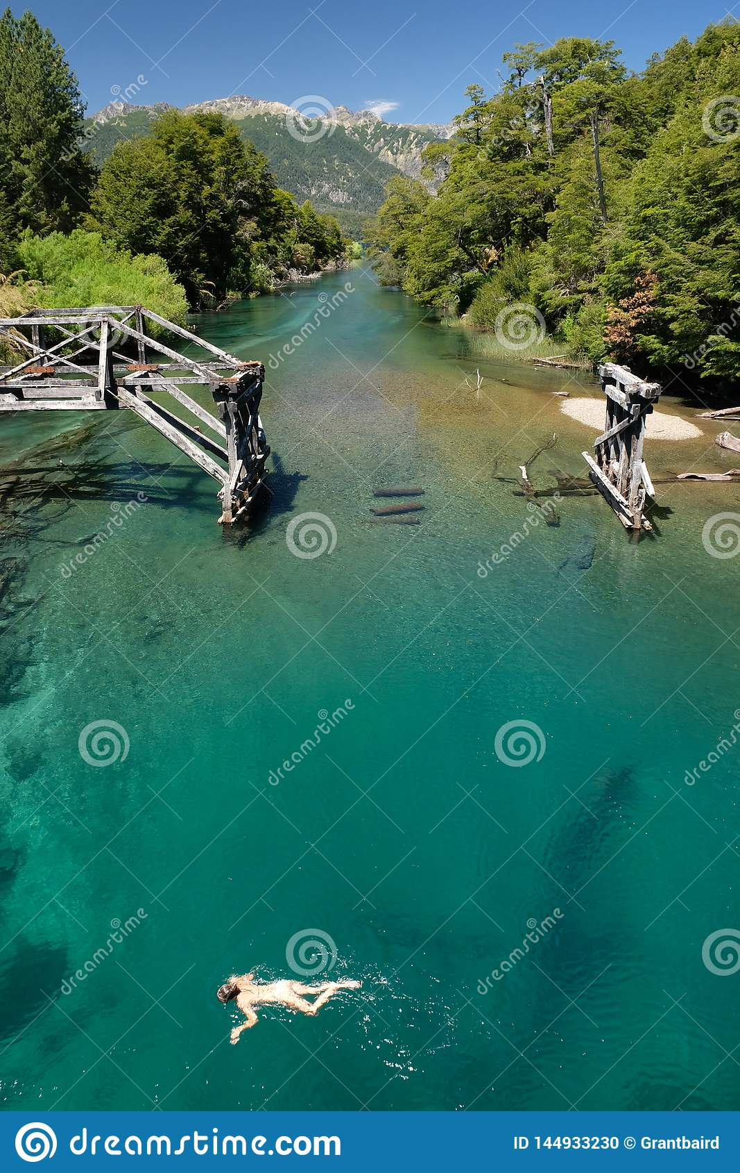 Acqua nella Patagonia, Argentina di Teal Green River con vecchio nuoto 2 della ragazza e del ponte