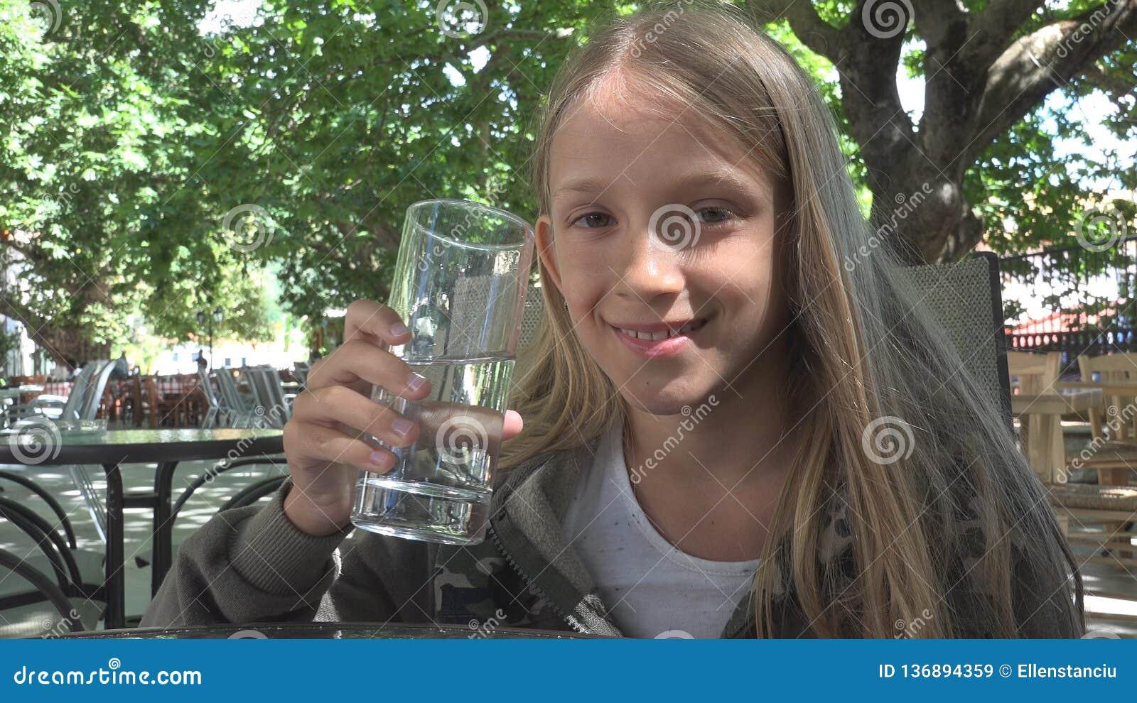 Acqua potabile del bambino al ristorante, bambino che tiene un bicchiere d acqua, sorridere della ragazza