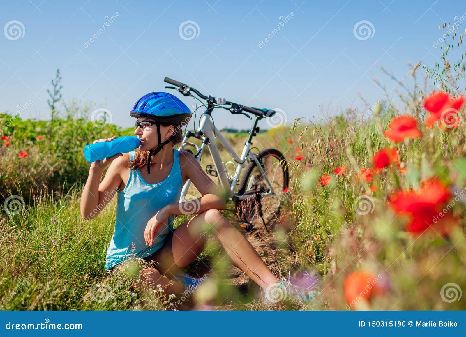 Acqua potabile del ciclista felice della giovane donna e resto avere dopo la guida della bicicletta nel campo di estate
