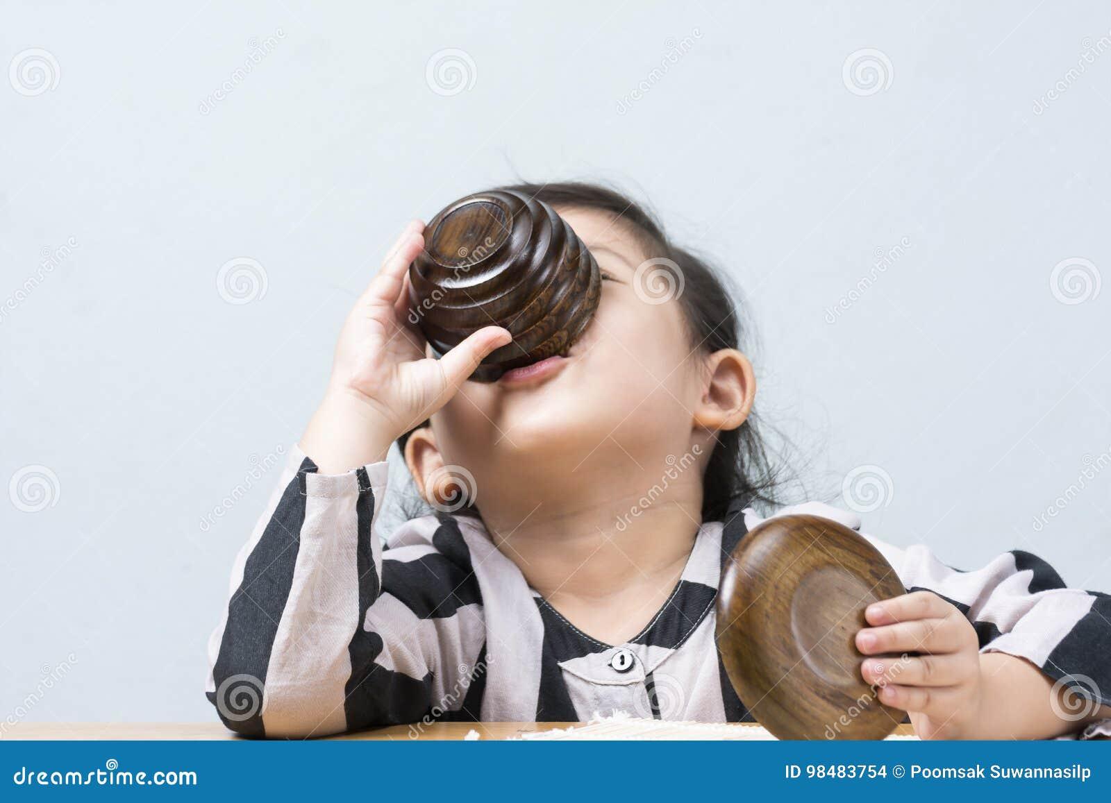 Acqua potabile della bambina tailandese asiatica sveglia dalla tazza di tè