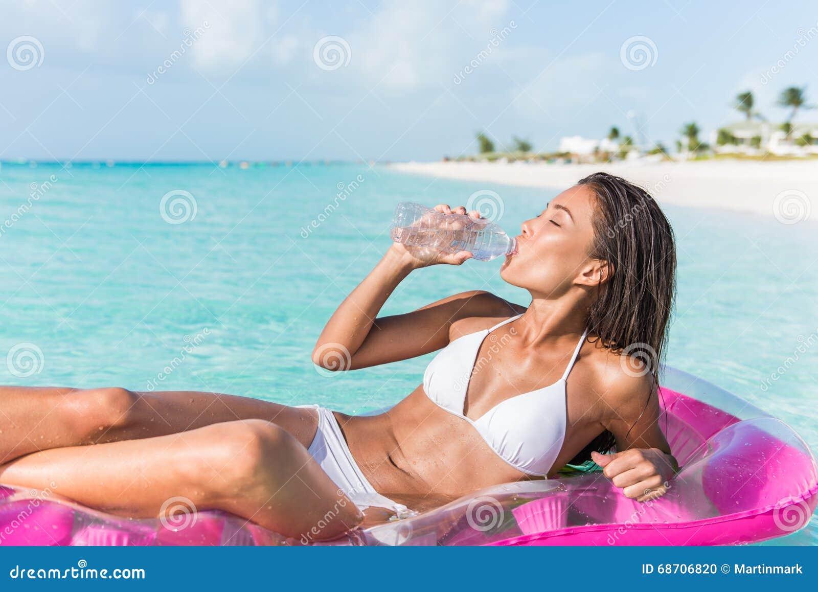 Acqua potabile della donna della spiaggia sulla vacanza caraibica