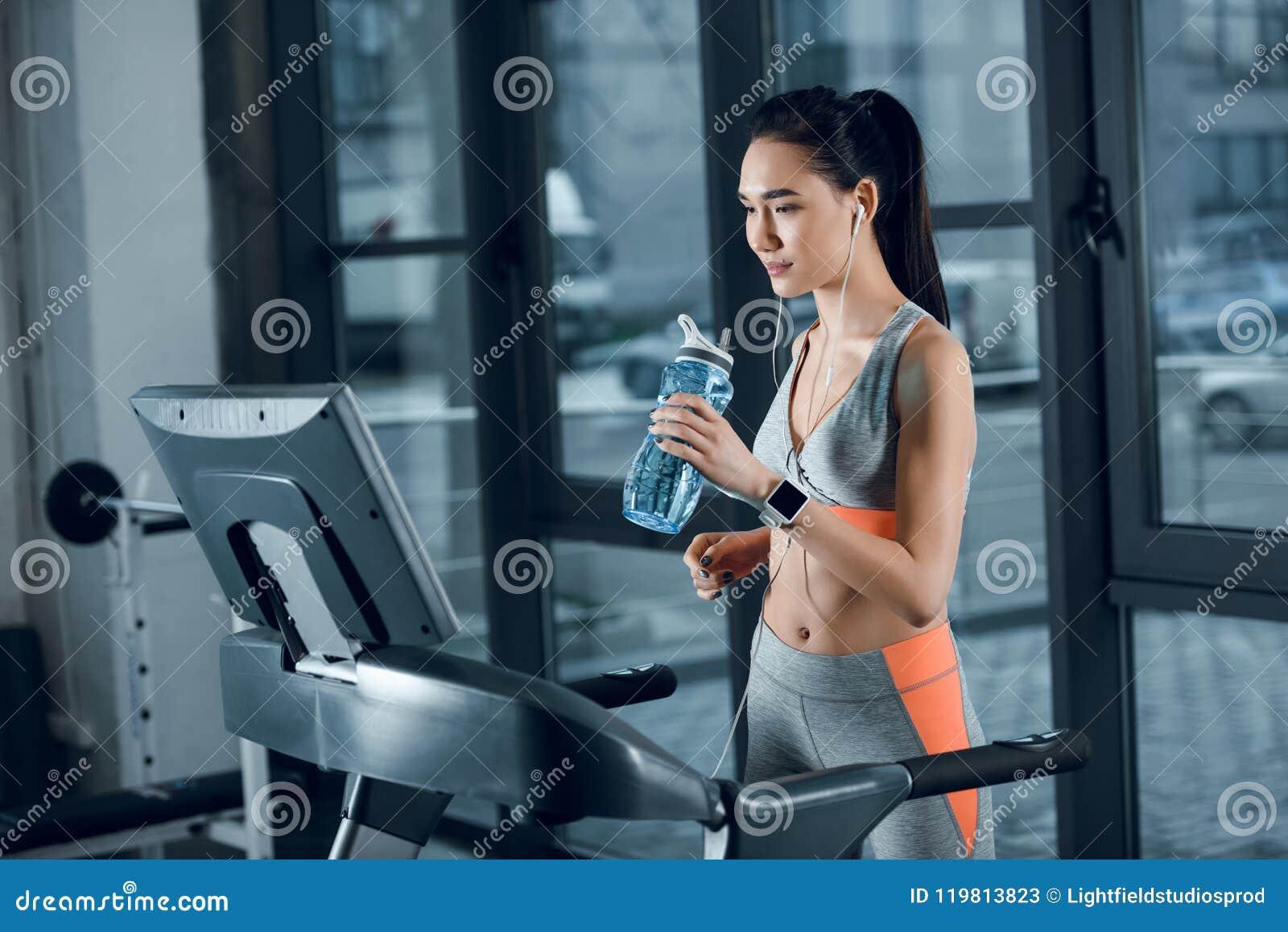 Acqua potabile della sportiva atletica giovane mentre pareggiando sulla pedana mobile