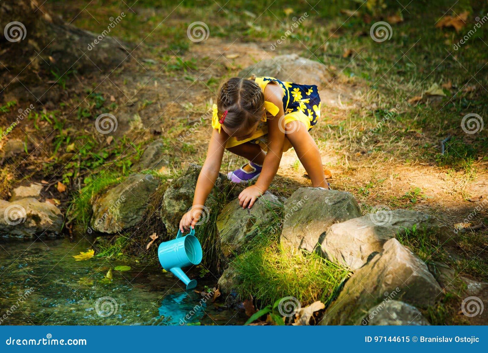 Acqua sveglia di tiraggio della bambina in secchio dalla corrente