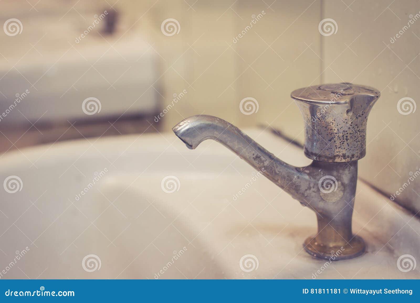 Acque di rifiuto, rubinetto di acqua nella toilette pubblica sporca