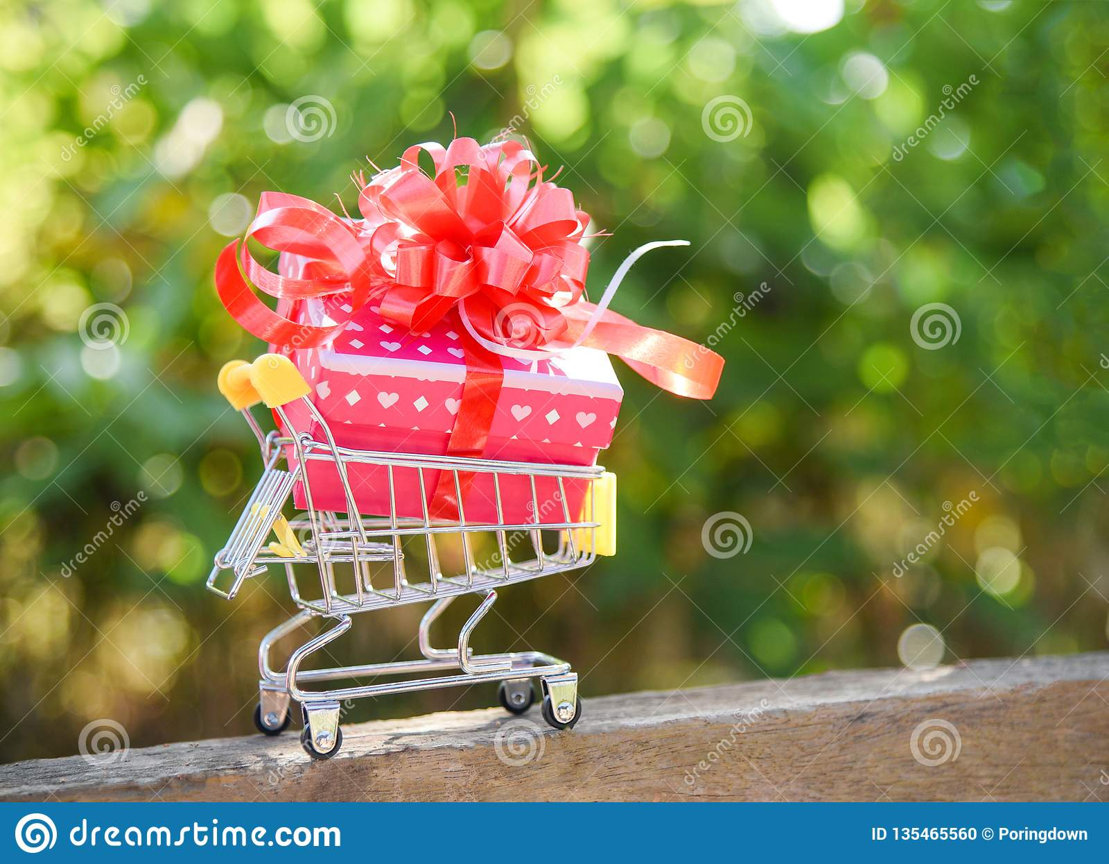 Acquisto di giorno di biglietti di S. Valentino e contenitore attuale di contenitore di regalo con l arco rosso del nastro sulla