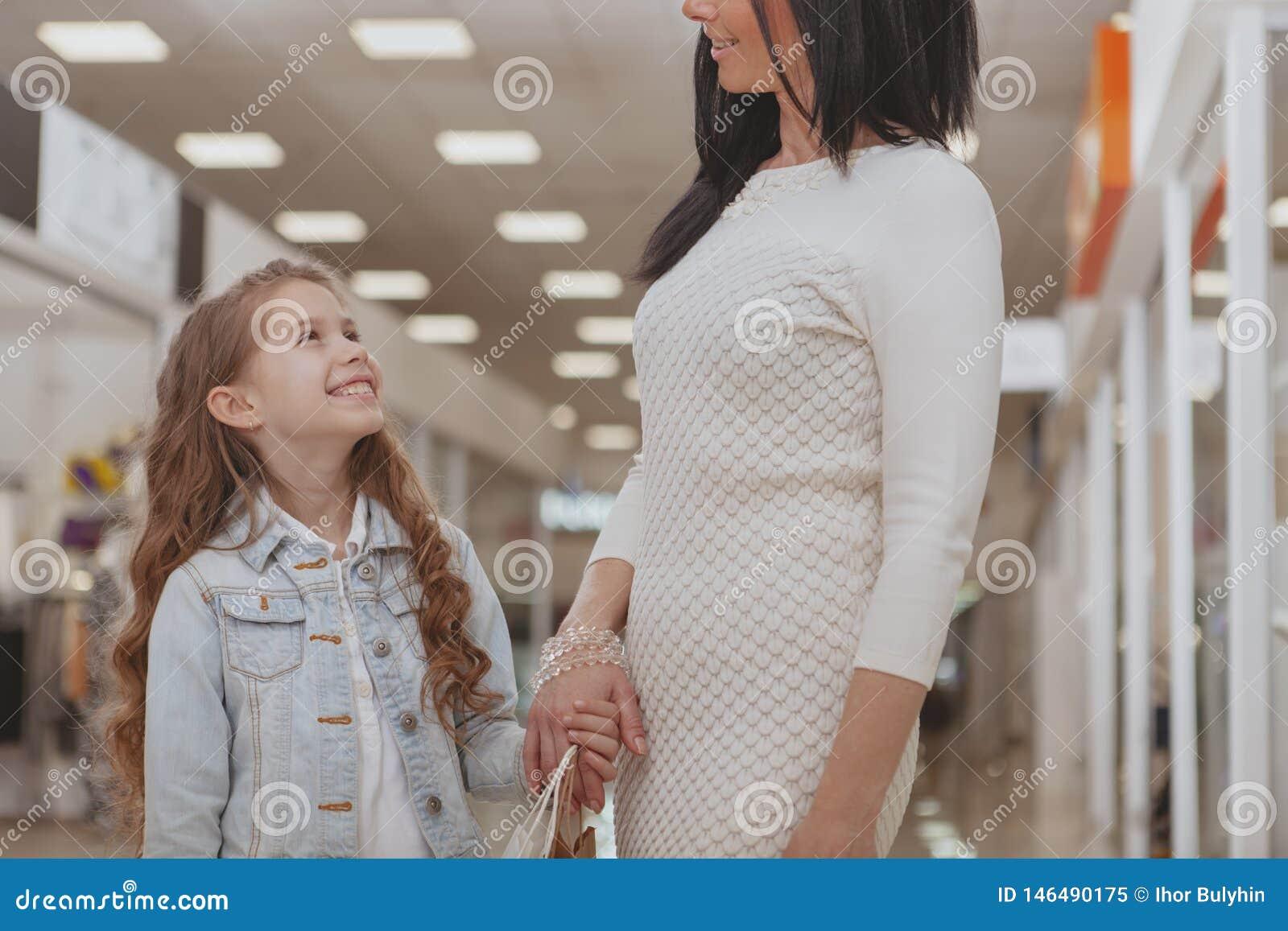Acquisto sveglio della bambina al centro commerciale con sua madre