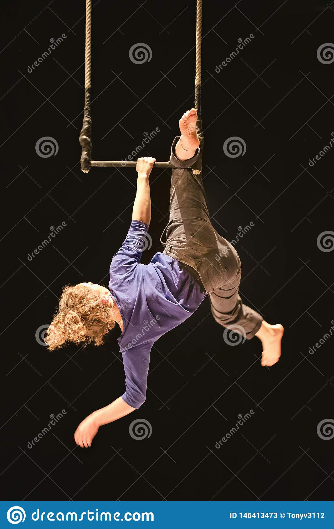 Acrobate féminin accrochant sur une oscillation dans un cirque