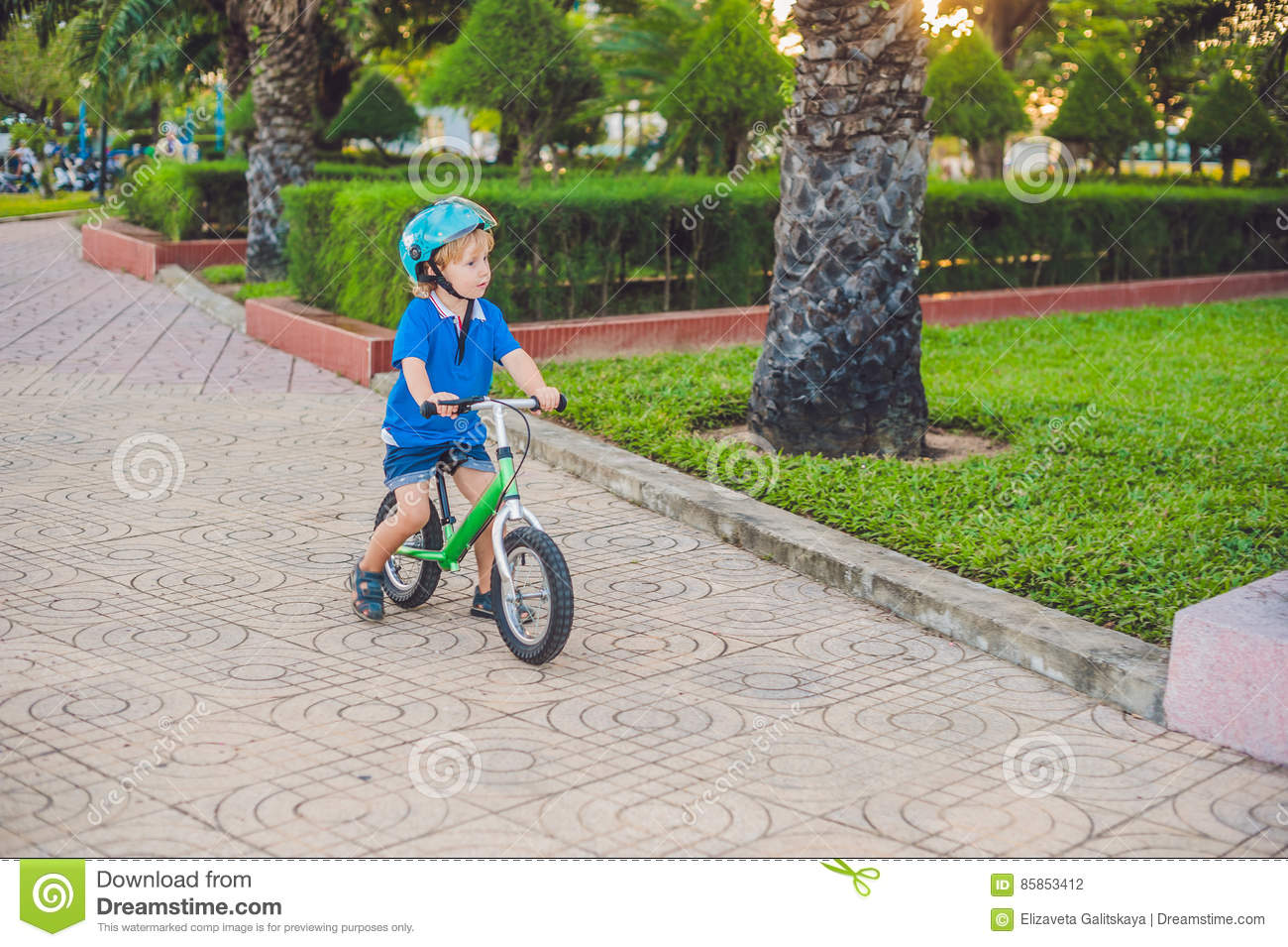 Active Blond Kid Boy Driving Bicycle In The Park Near The