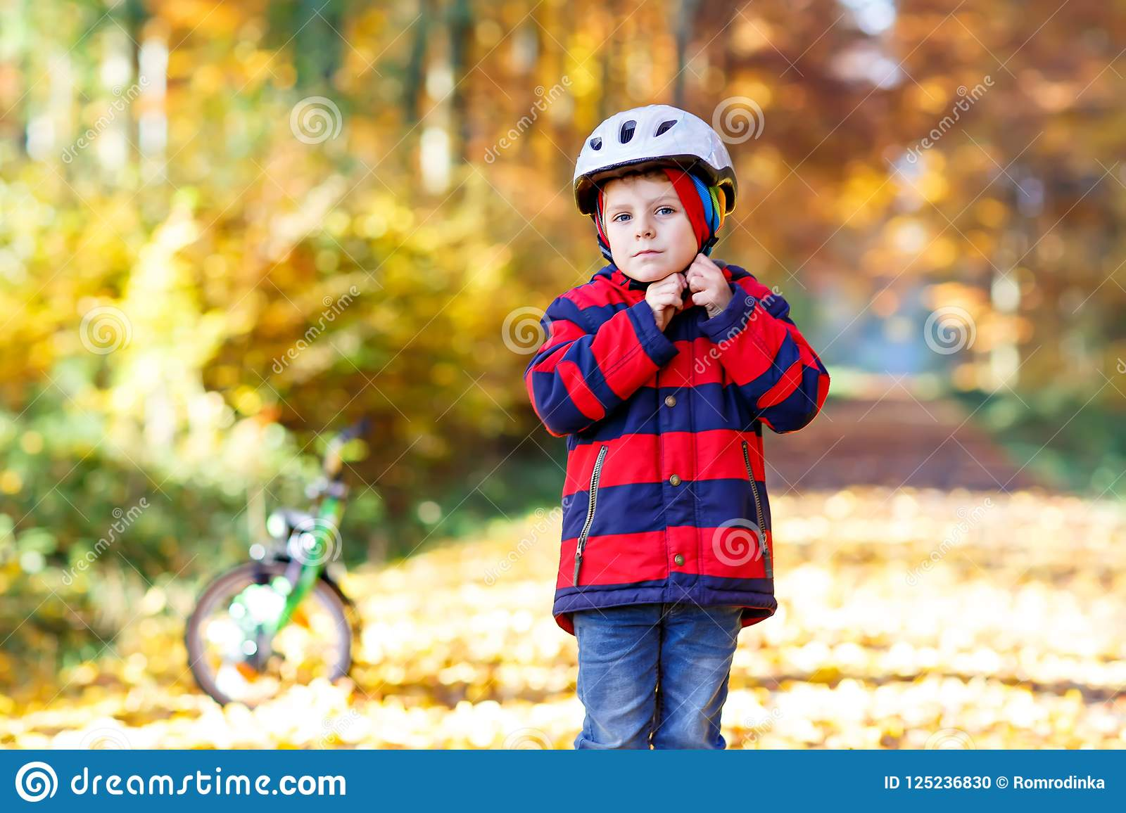Active child putting safe helmet before cycling on sunny fall day in nature.