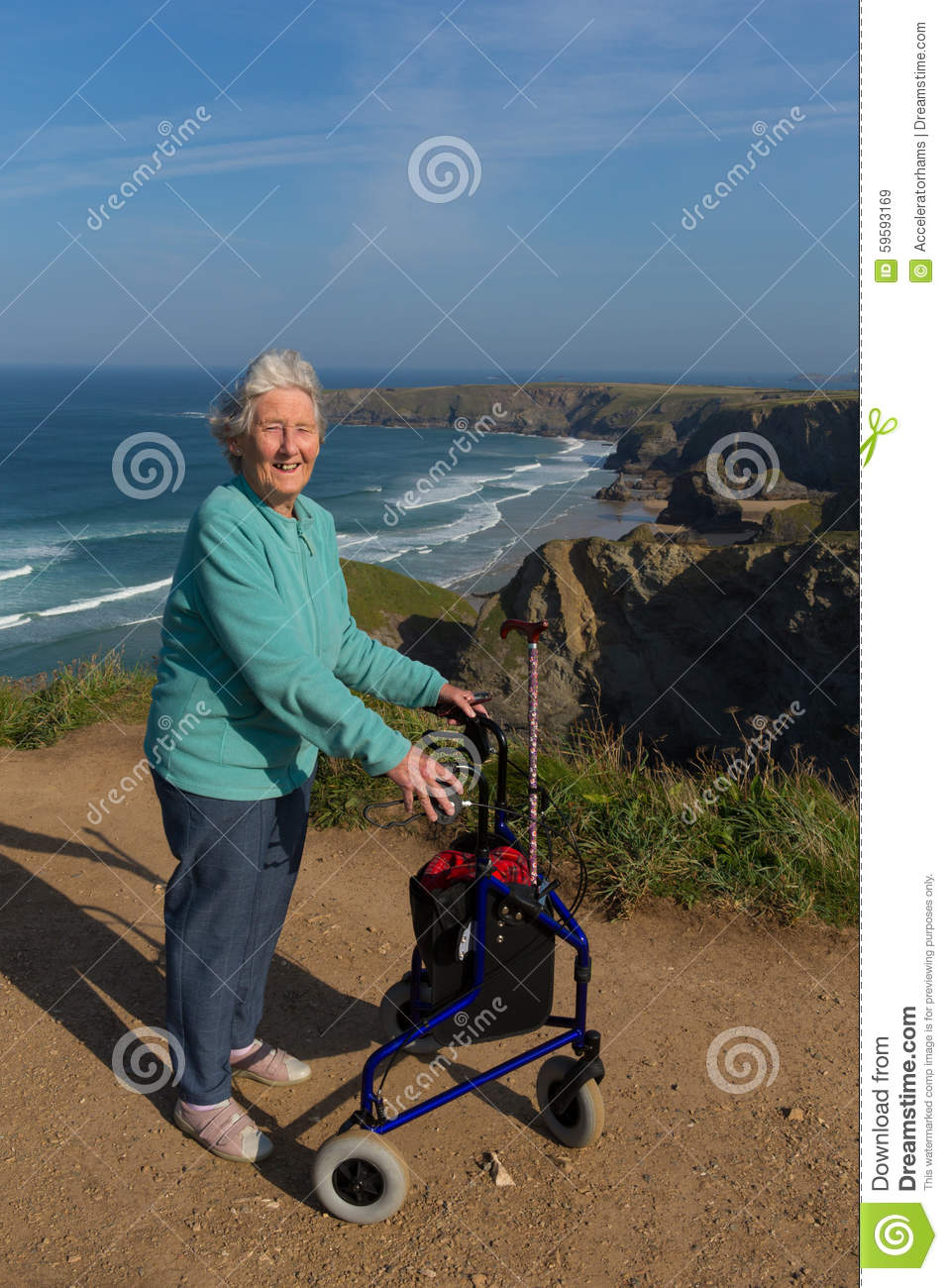 Active elderly lady pensioner in eighties with three wheel mobility frame by beautiful coast scene