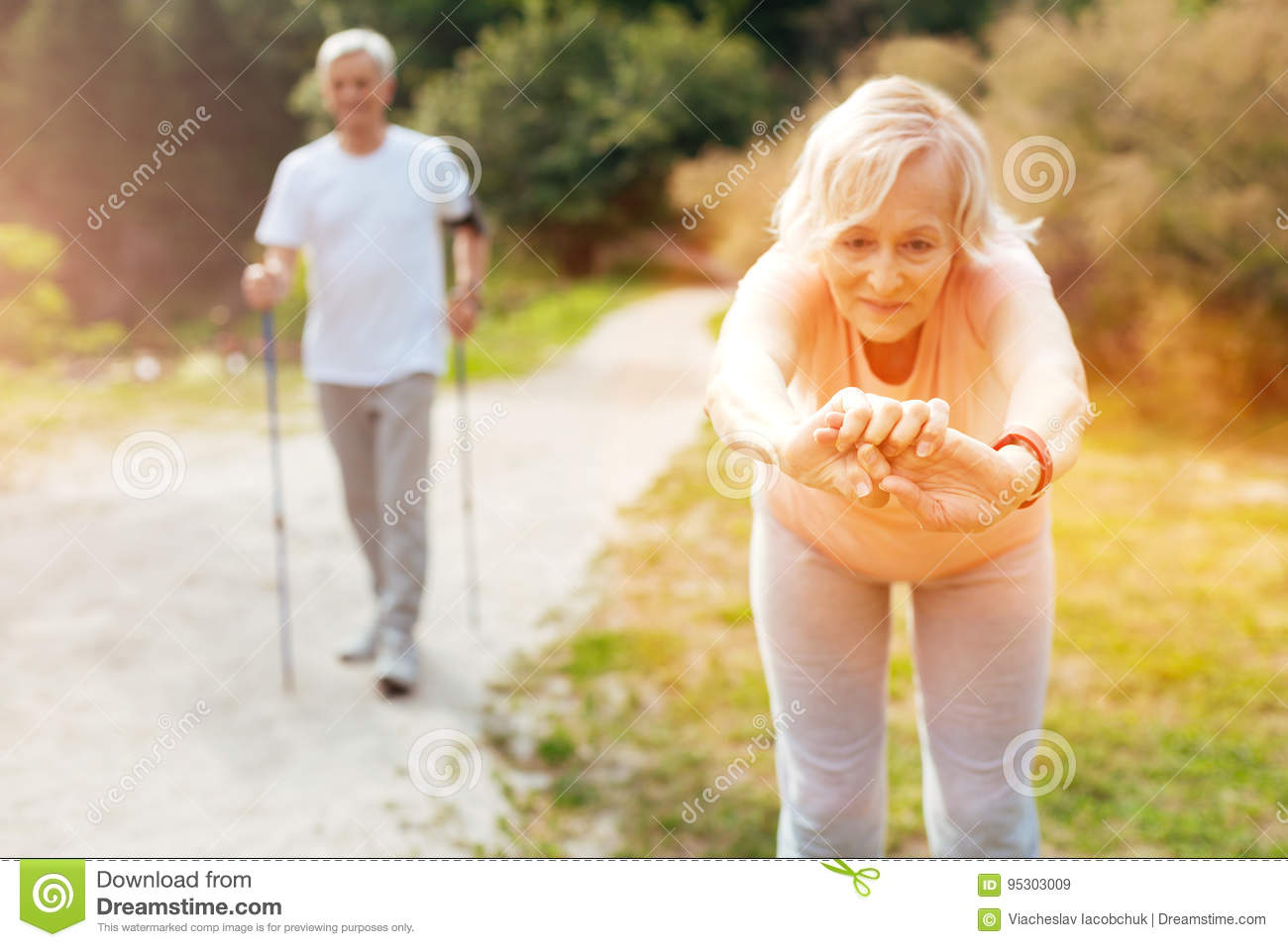 Active elderly woman doing a bending exercise