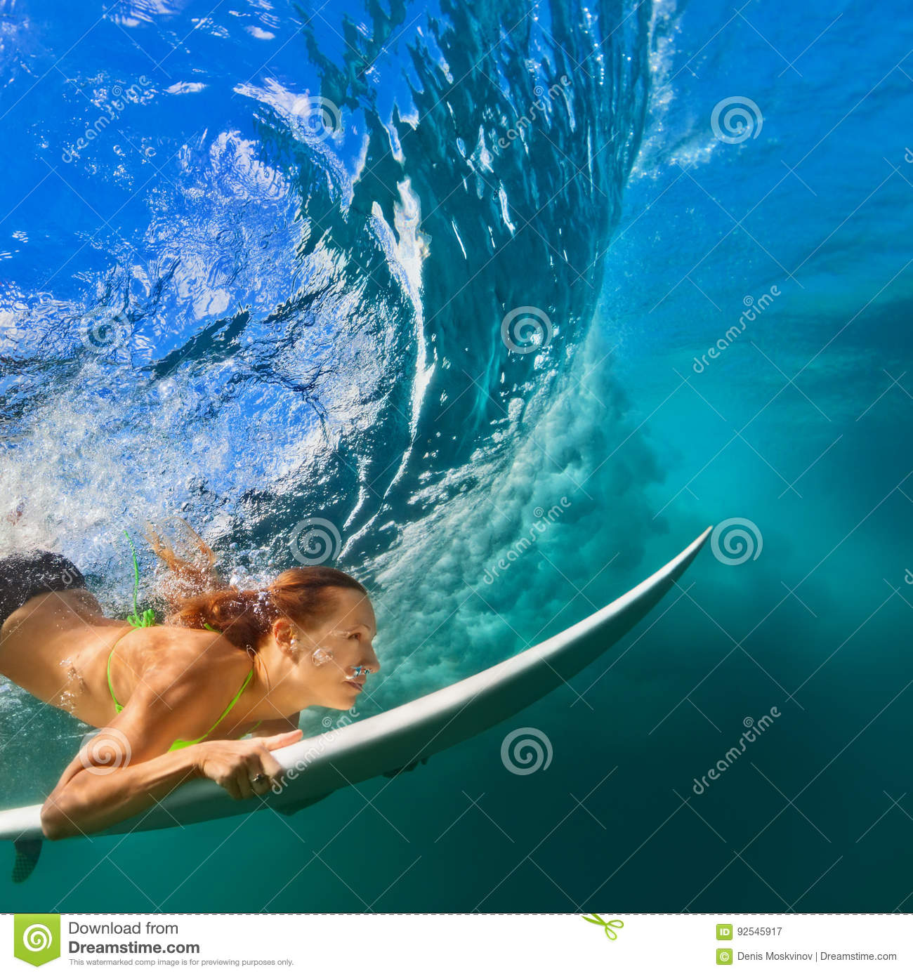 Active girl in bikini in dive action on surf board