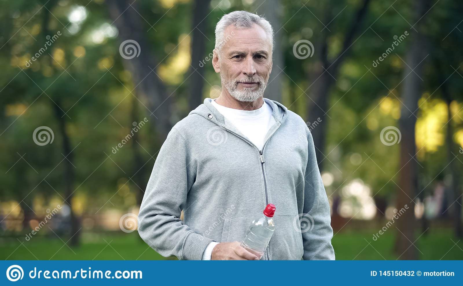Active grandfather drinking water after workout in park, health care, sport