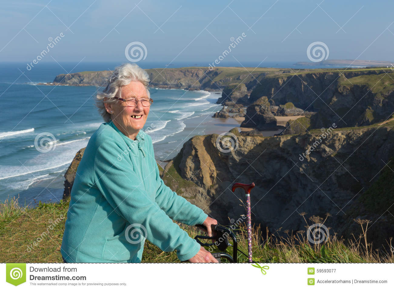 Active happy elderly female pensioner in eighties with mobility frame and walking stick by beautiful coast scene